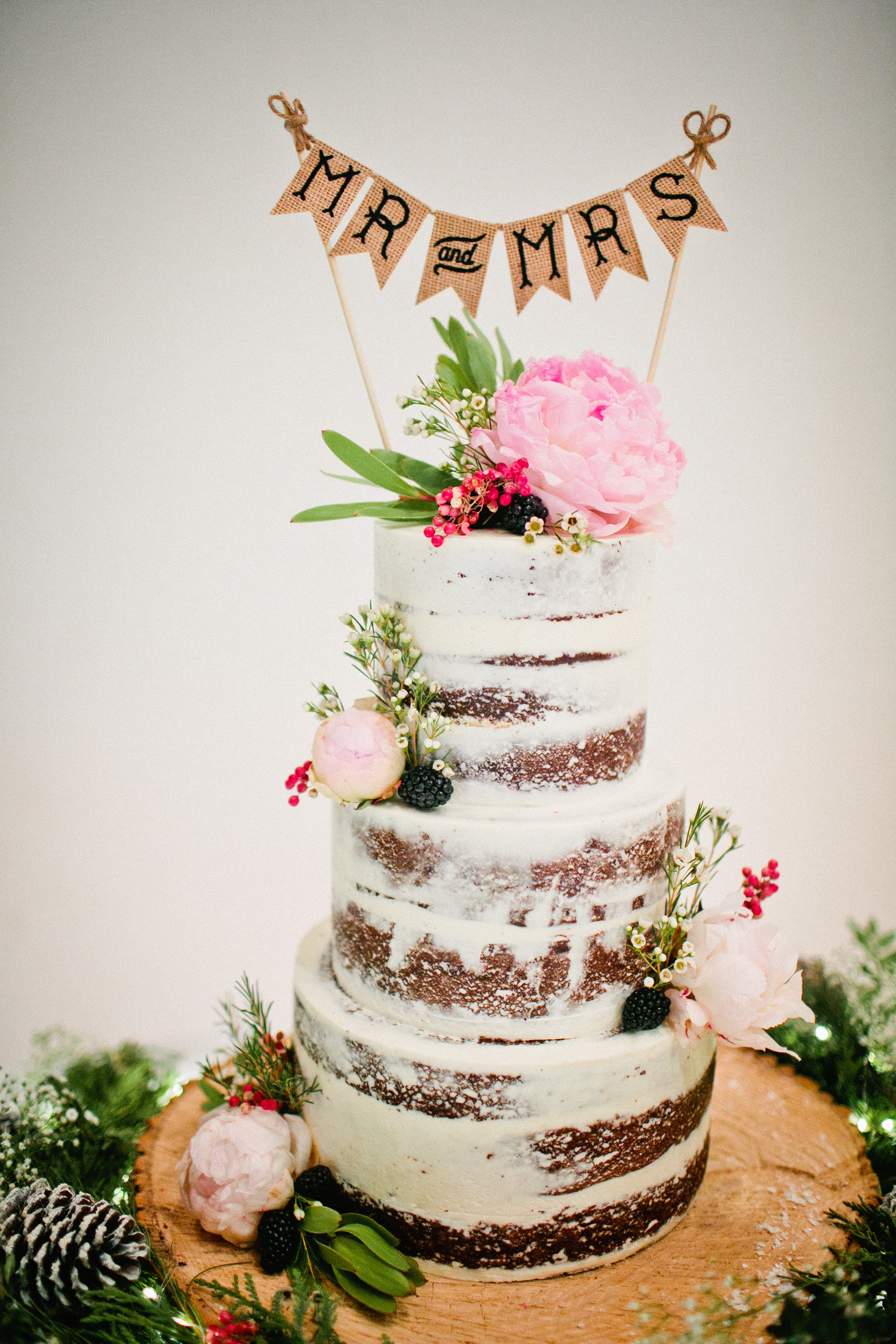 nearly naked wedding cake with pink flowers