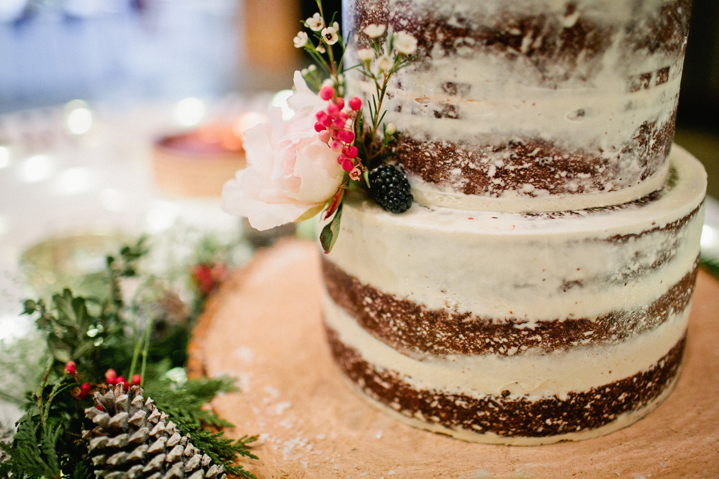 nearly naked wedding cake with fruit and flowers