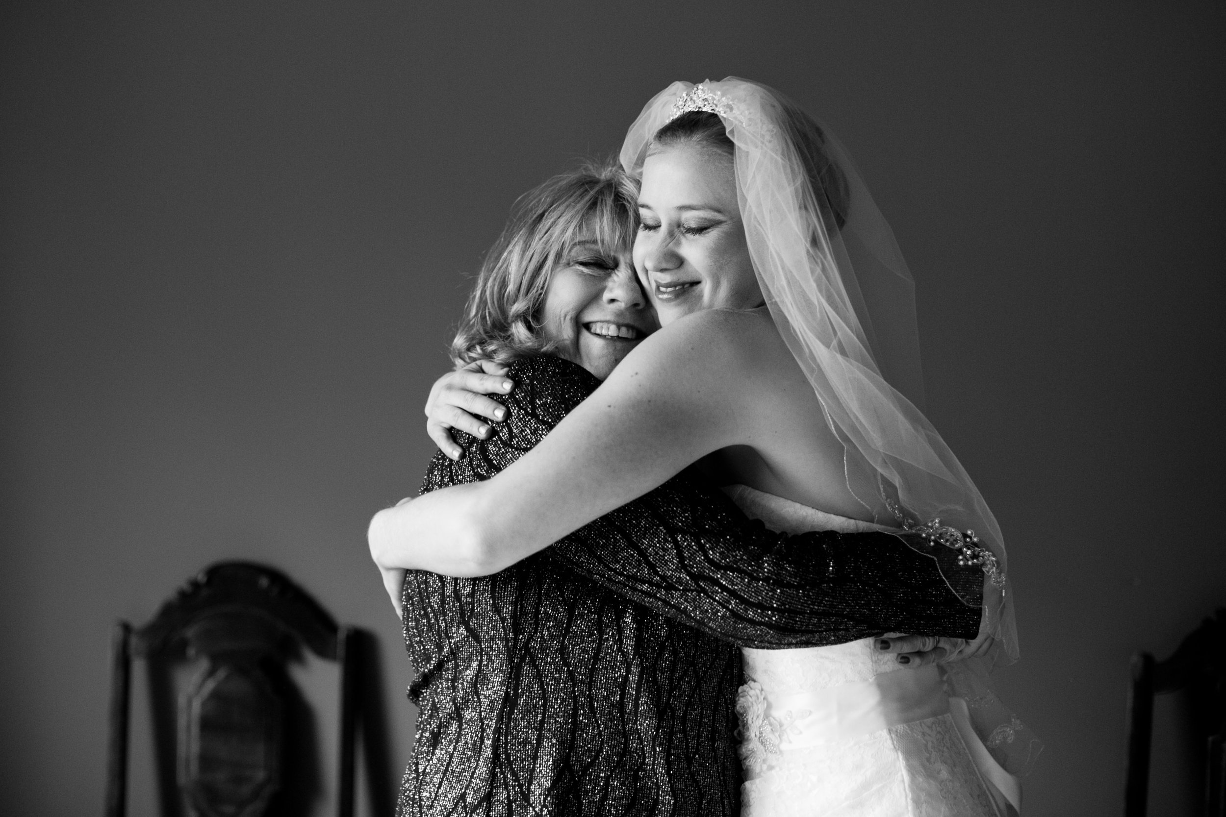 a sweet mother-daughter moment with bride Jenny after getting into her dress and veil