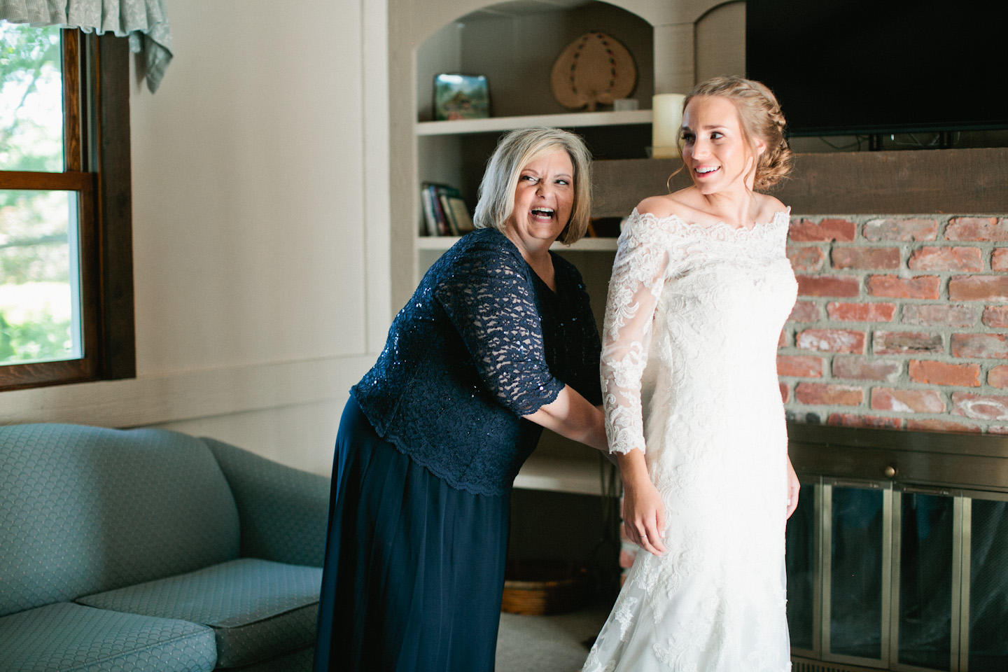 mother of bride helping bride into dress in omaha air bnb