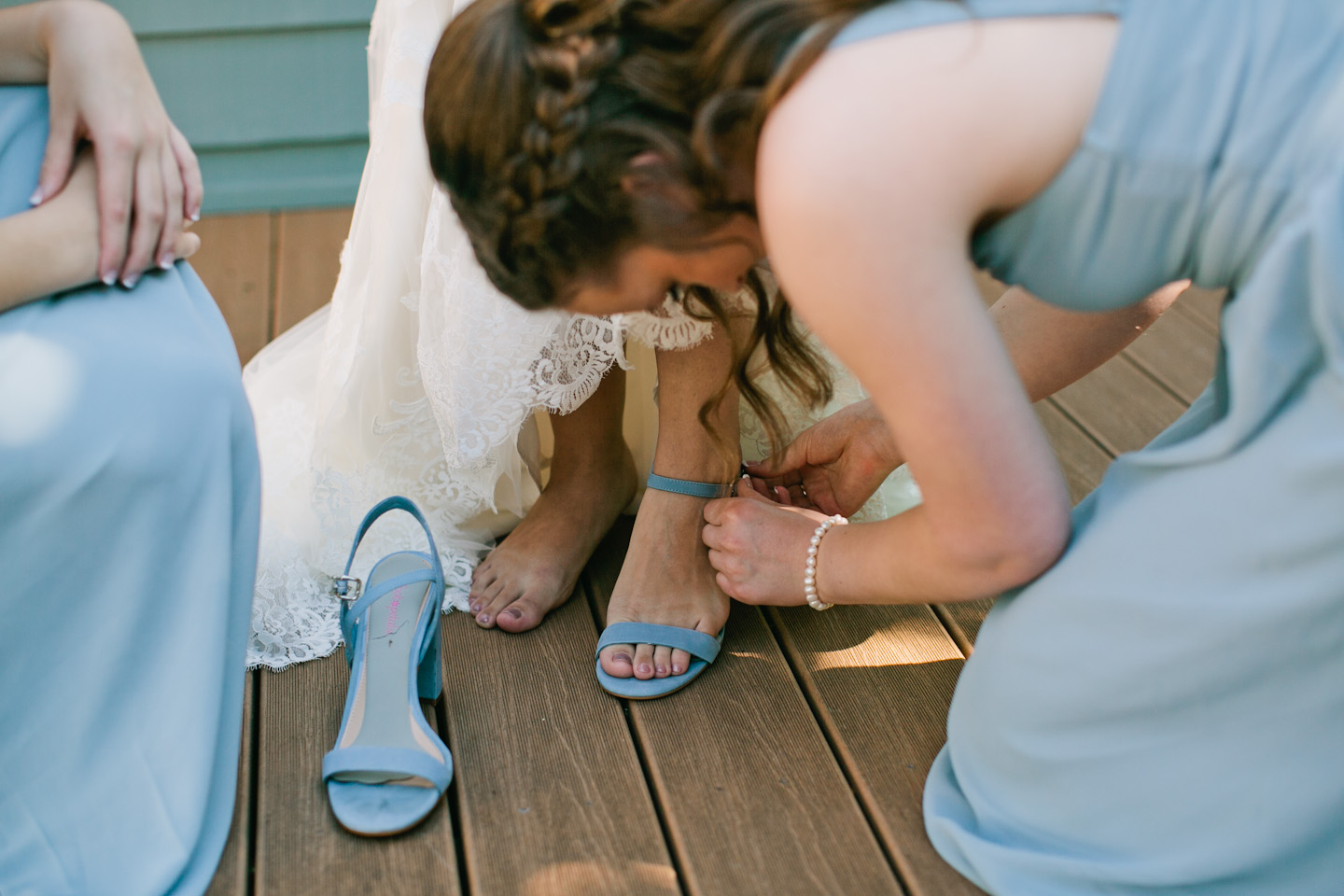 sisters helping bride put on her blue suede wedding shoes