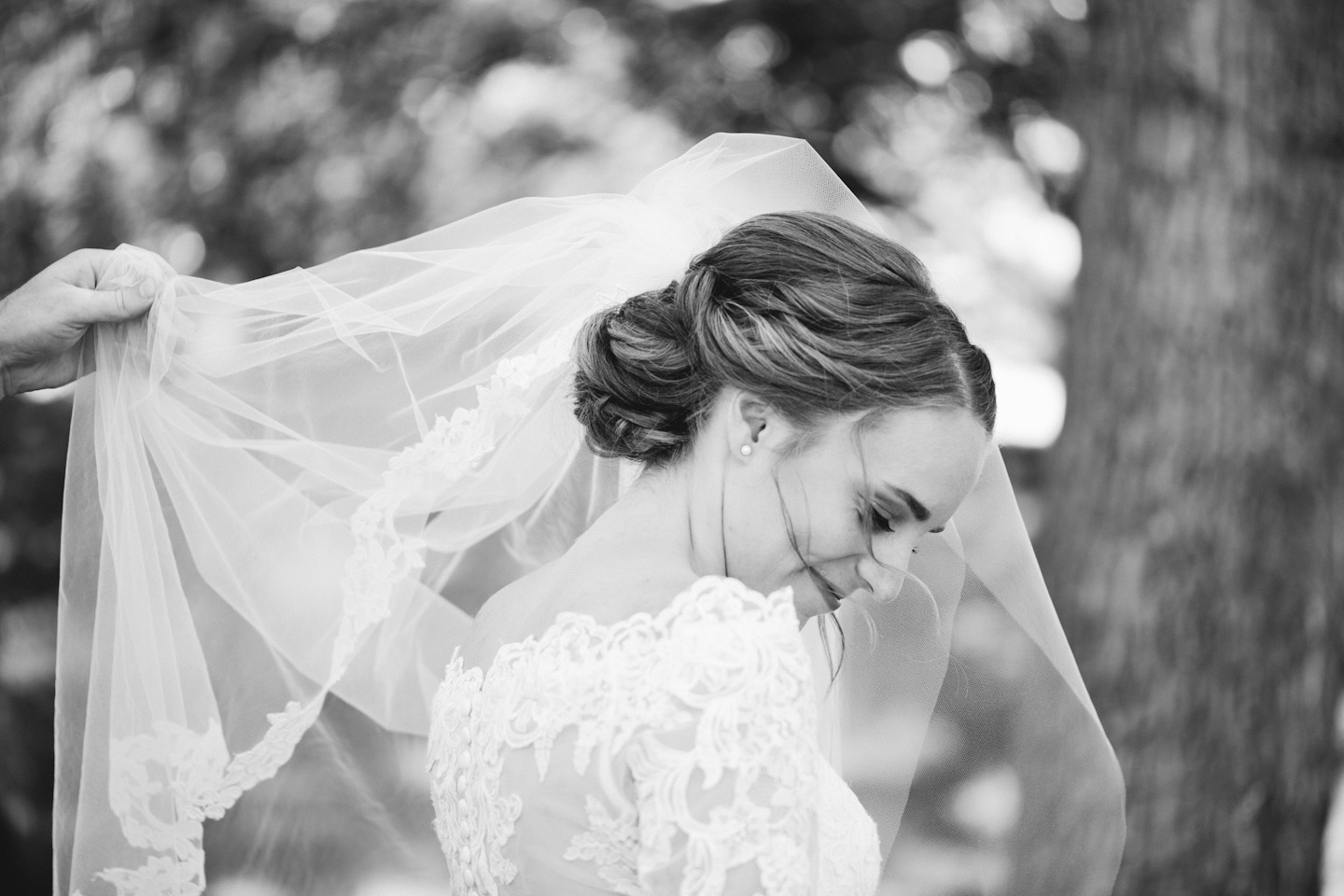 photo of groom holding bride's wedding veil in the wind