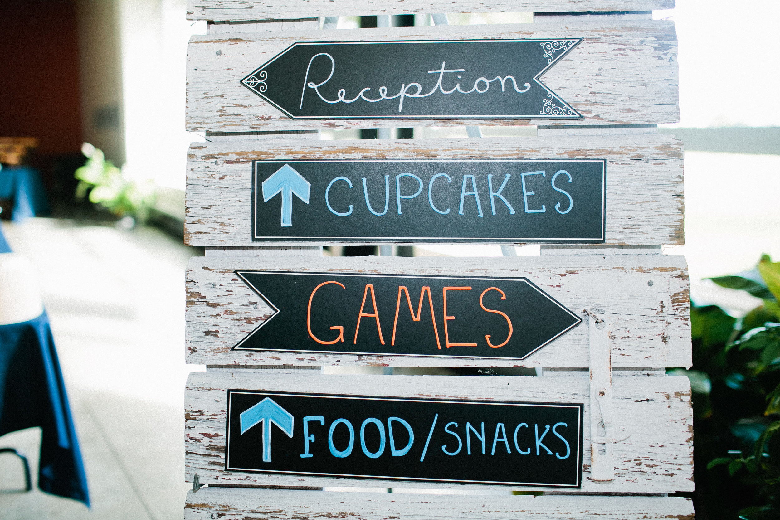 rustic sign at wedding reception games food cupcakes