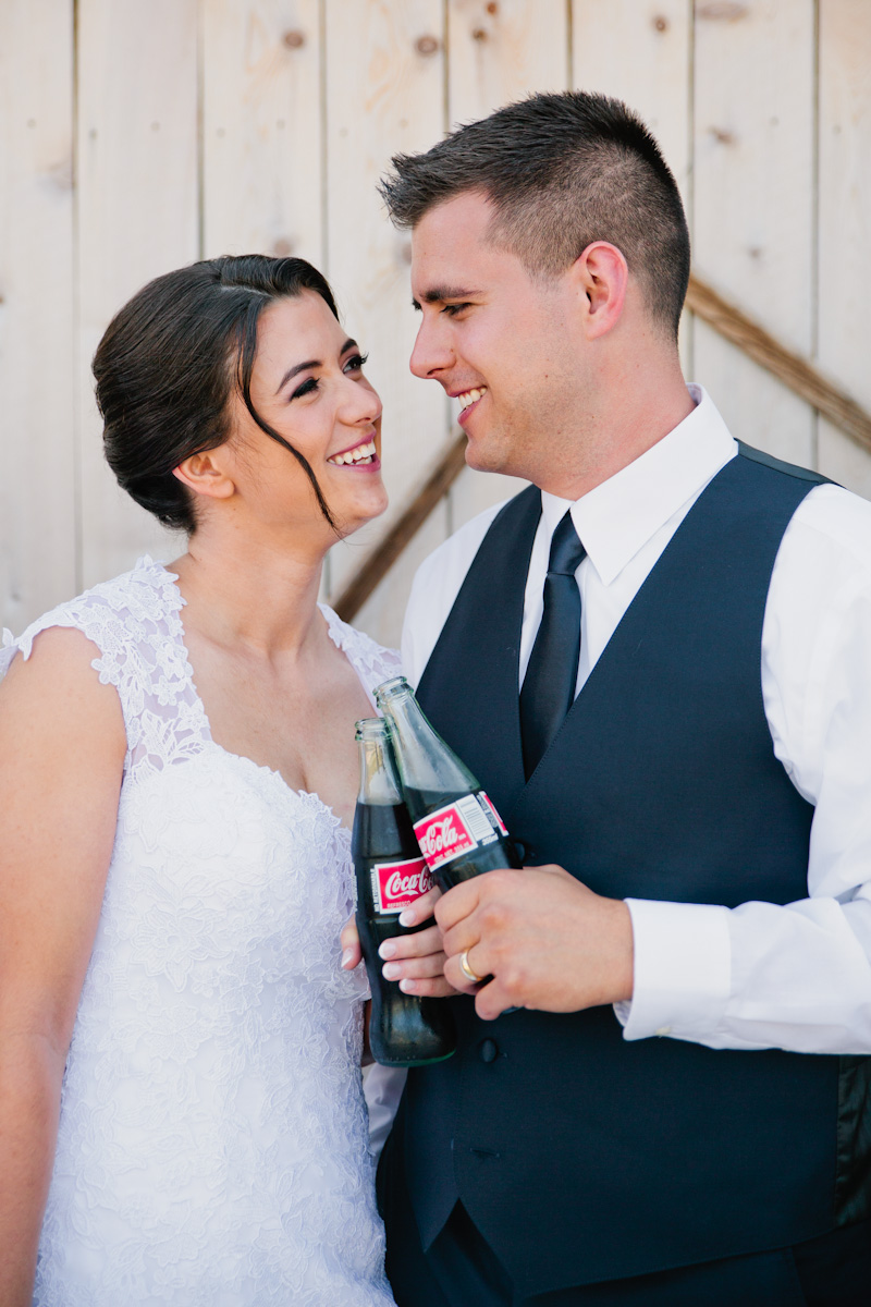 bride and groom toasting with coke bottles on wedding day photos