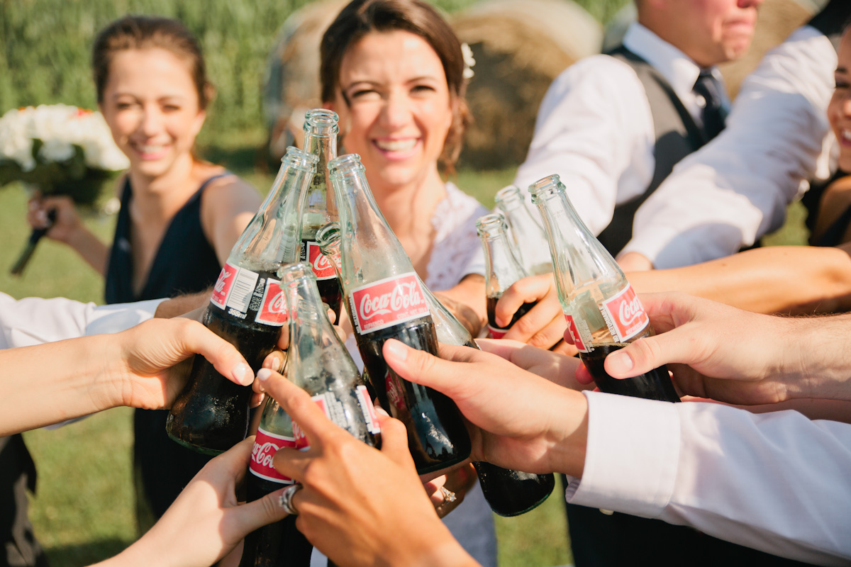 bride laughing while toasting wedding party with coke bottles