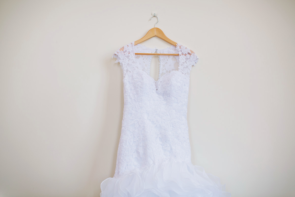 white wedding dress hanging on plain wall and wooden bride hanger