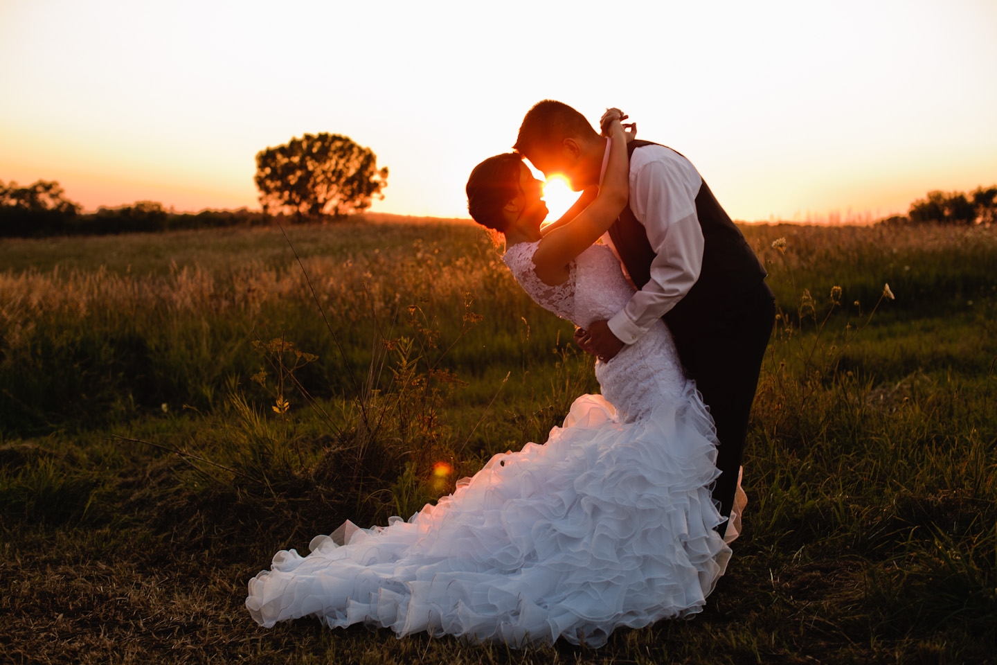 couple kissing with sunflare des moines iowa field