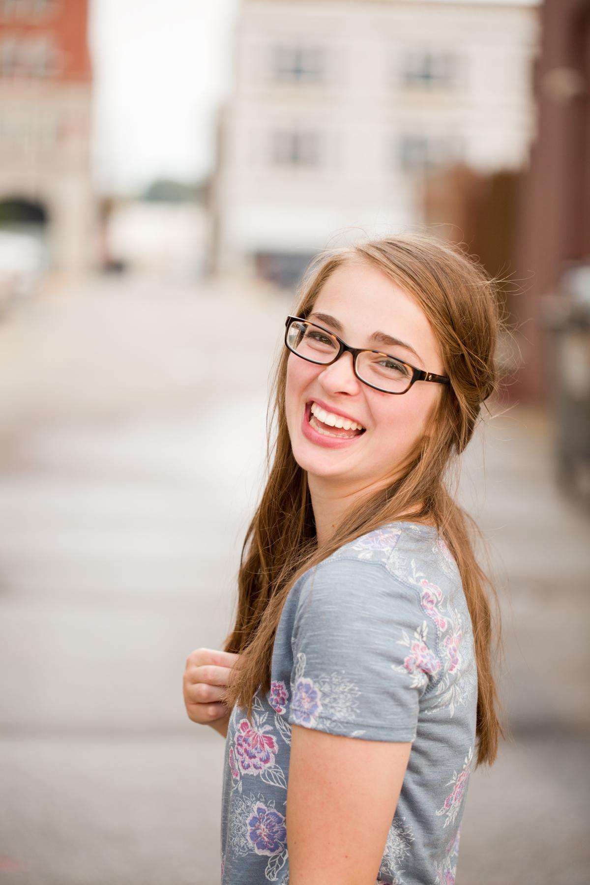 senior girl laughing in alley in cedar falls senior pictures