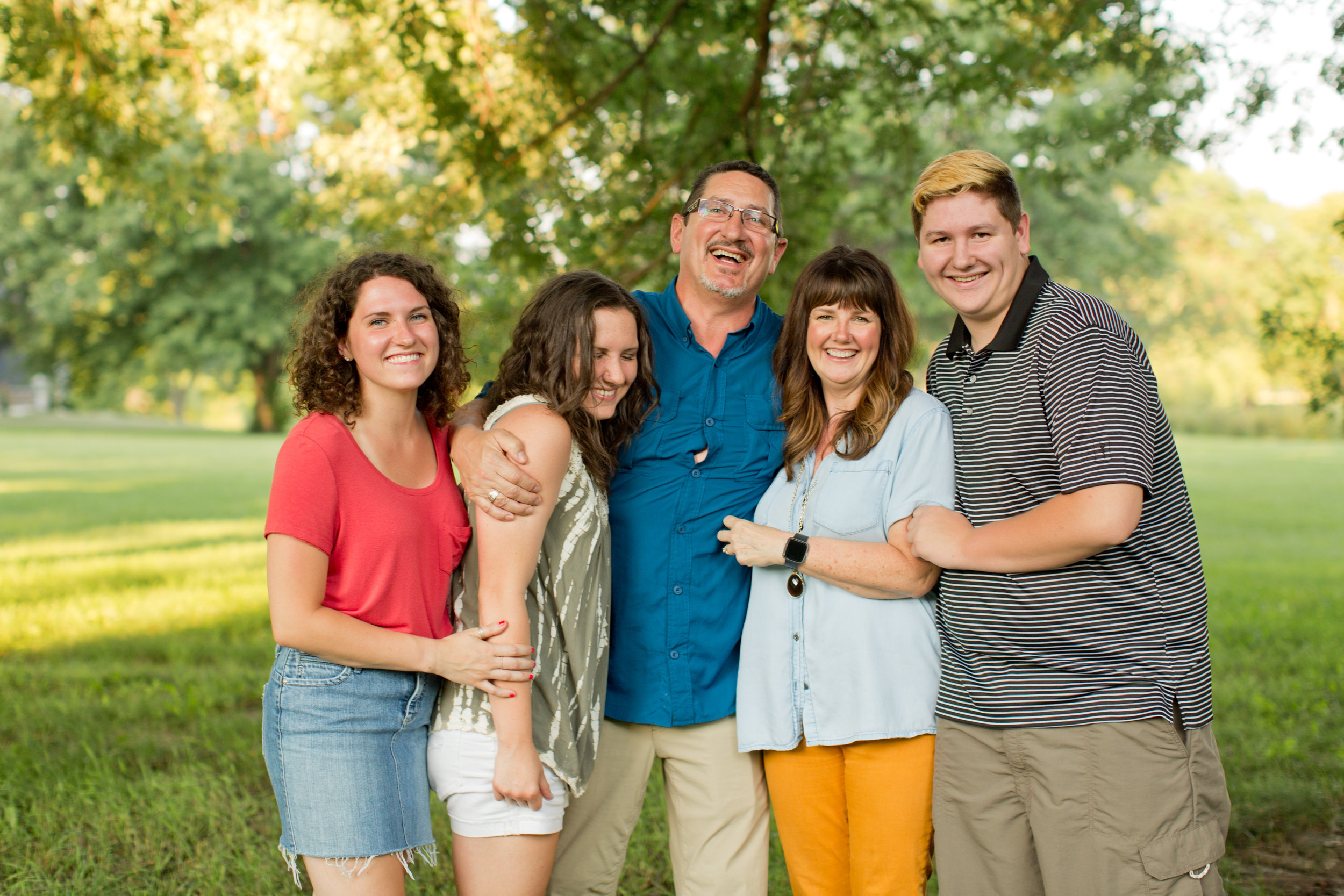 family hugging and laughing during family pictures