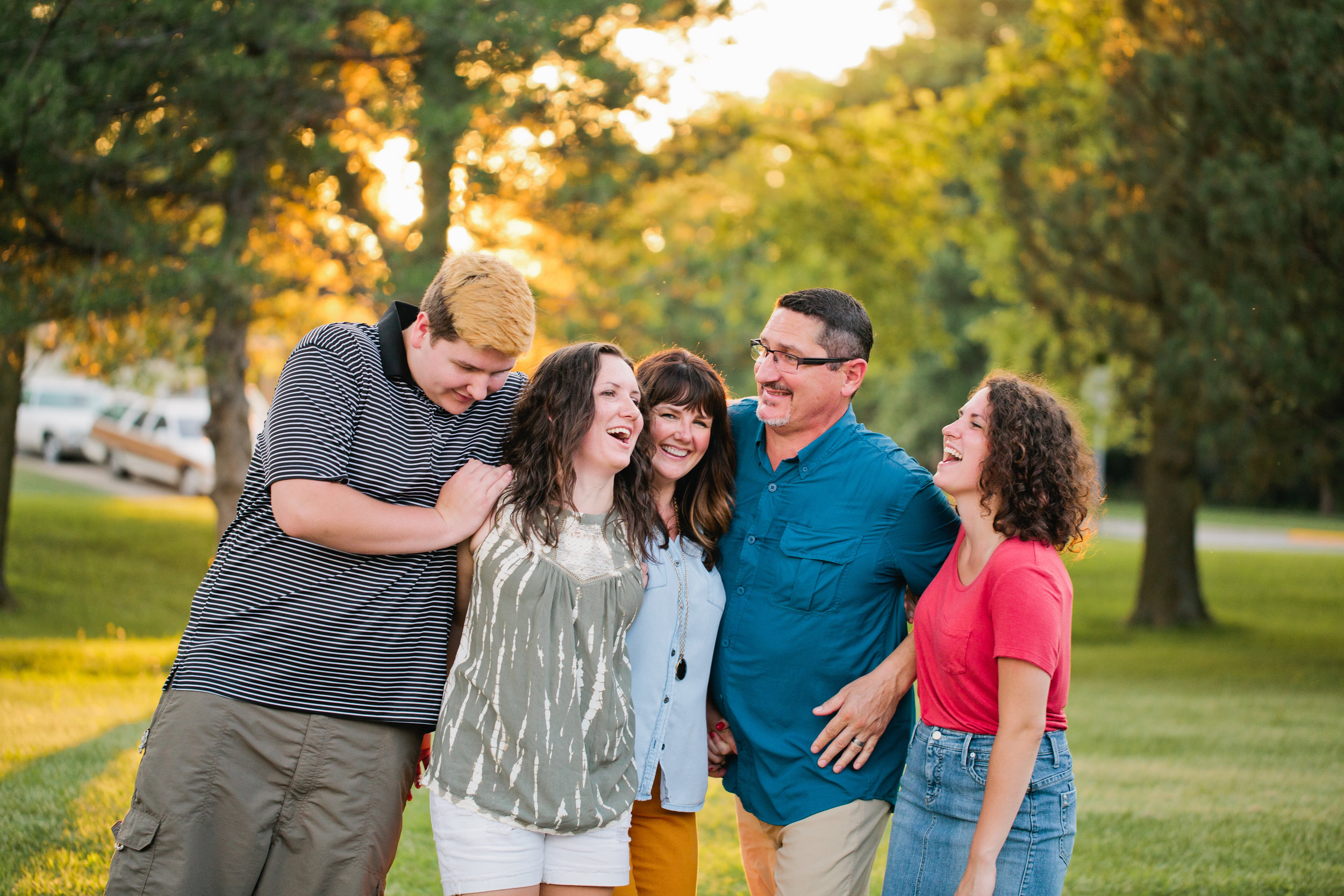 family laughing in park at sunset during family photography Des Moines parks Iowa