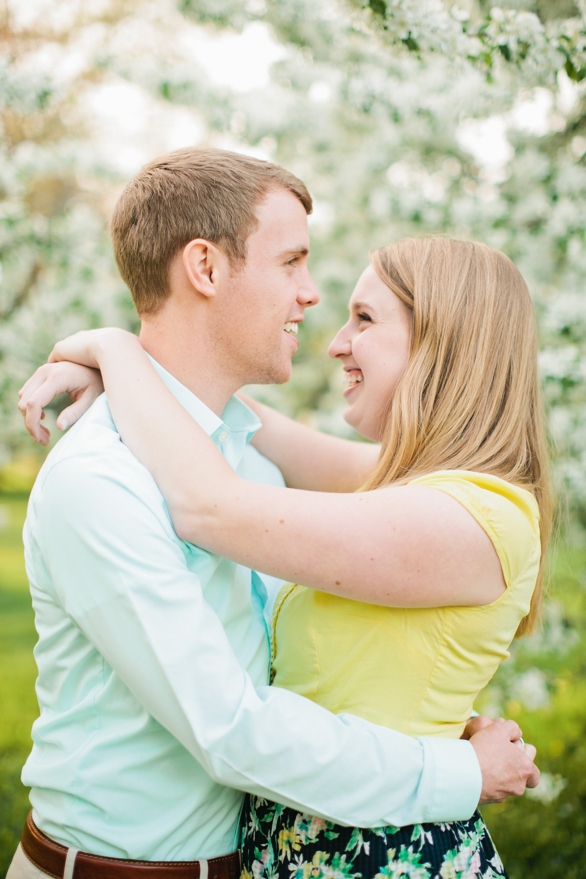 couple hugging in front of white cherry flowers in des moines park