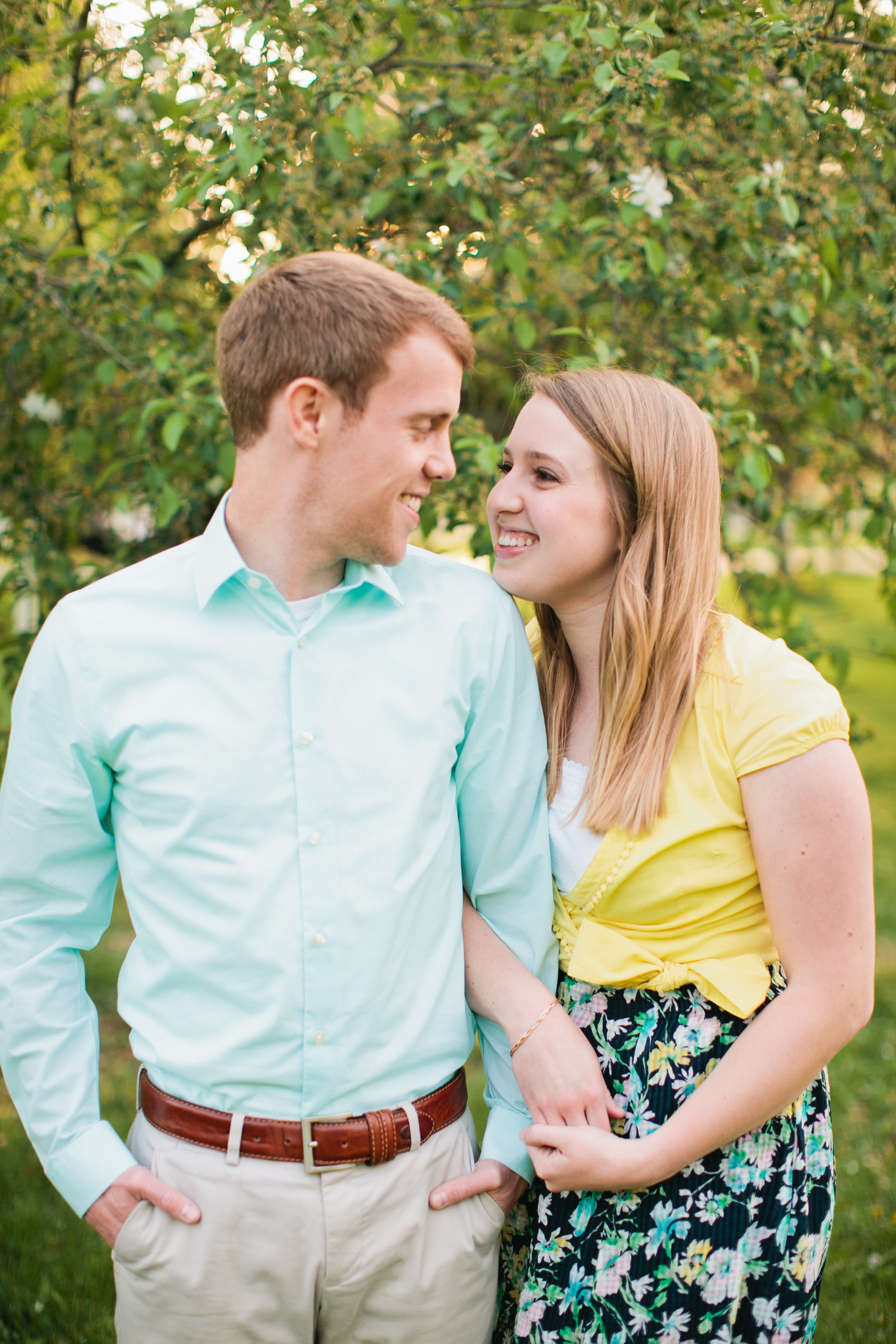 romantic photo of couple linking arms and smiling engagement pictures Des Moines