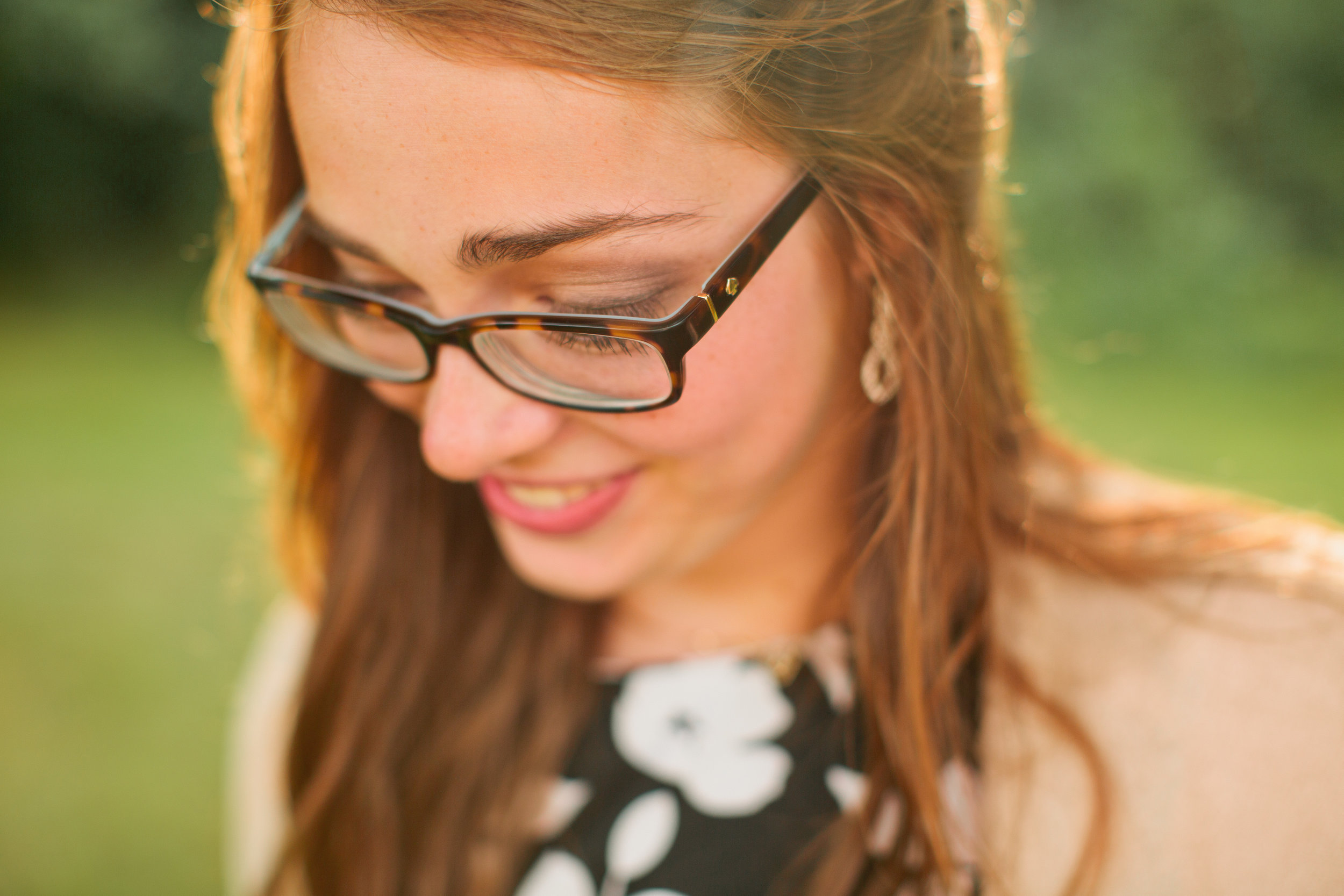 senior girl wearing glasses and earrings with curled hair senior pictures