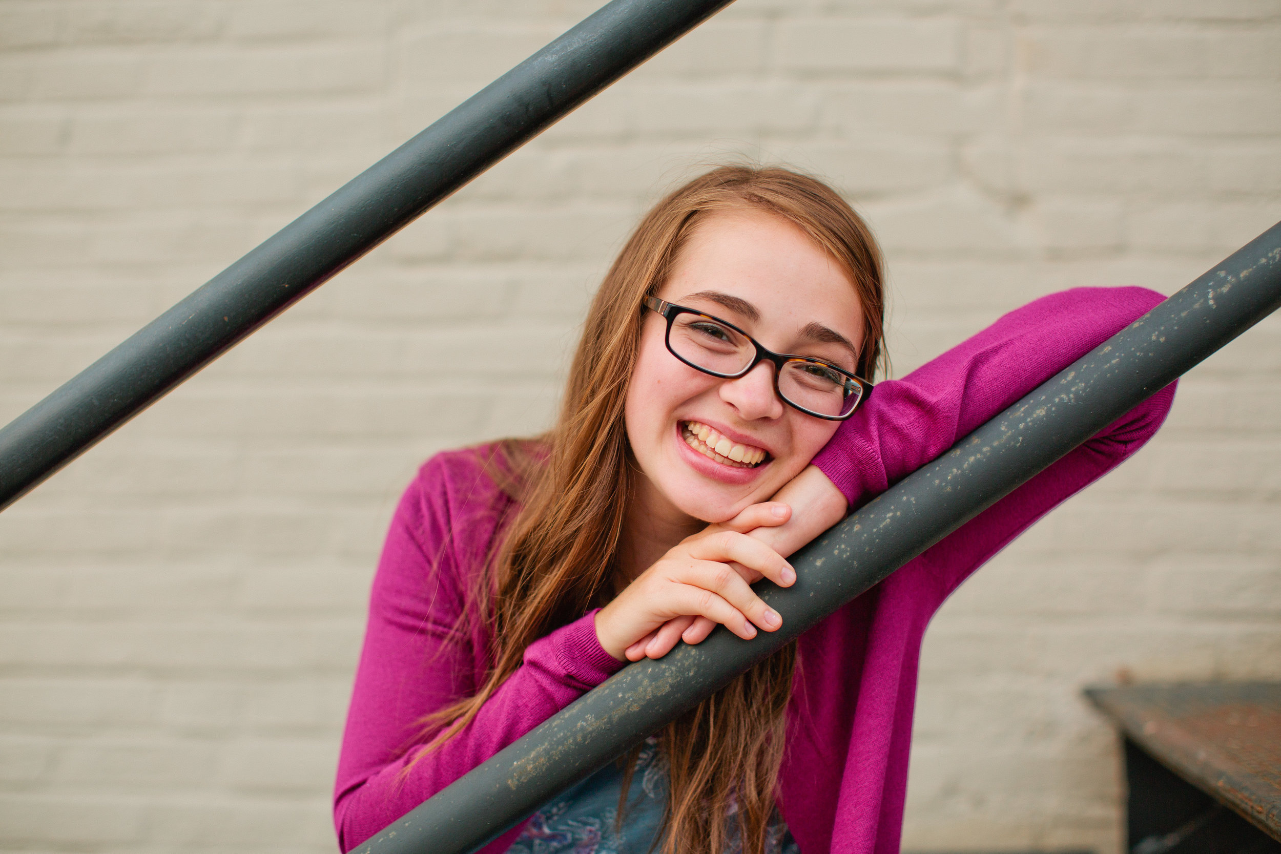 des moines senior photography on downtown metal stairs // hannah wearing glasses and laughing