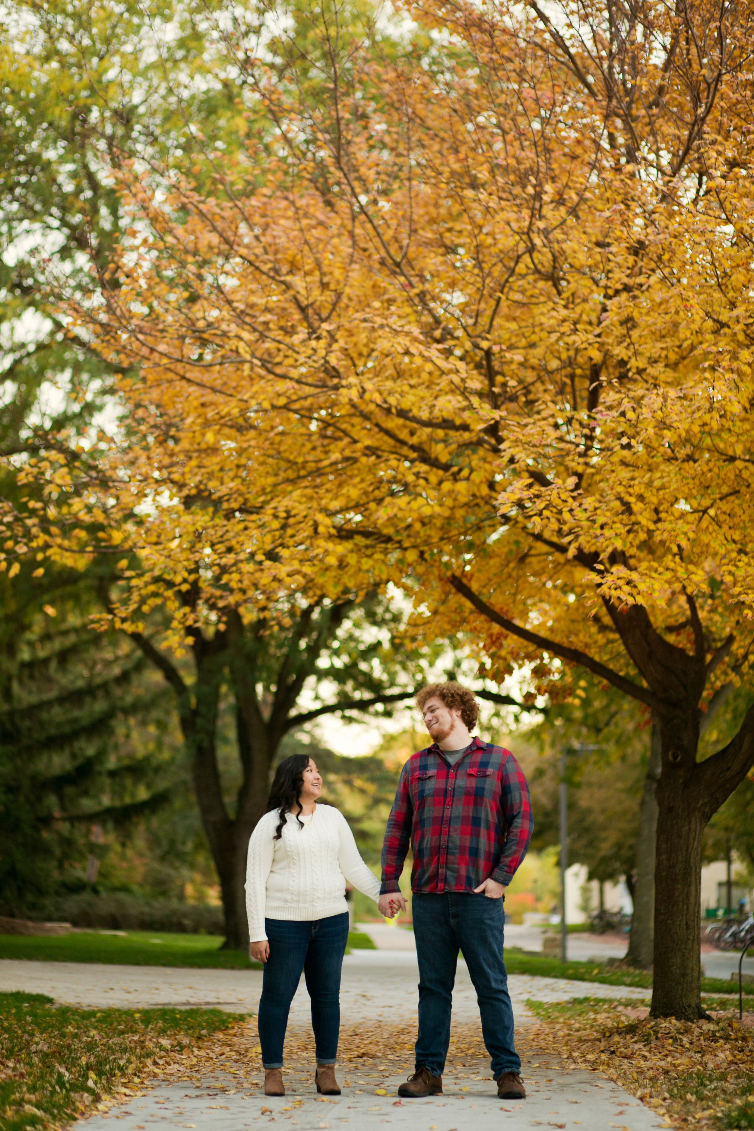 couple holding hands on Iowa State University campus in fall with leaves on the ground