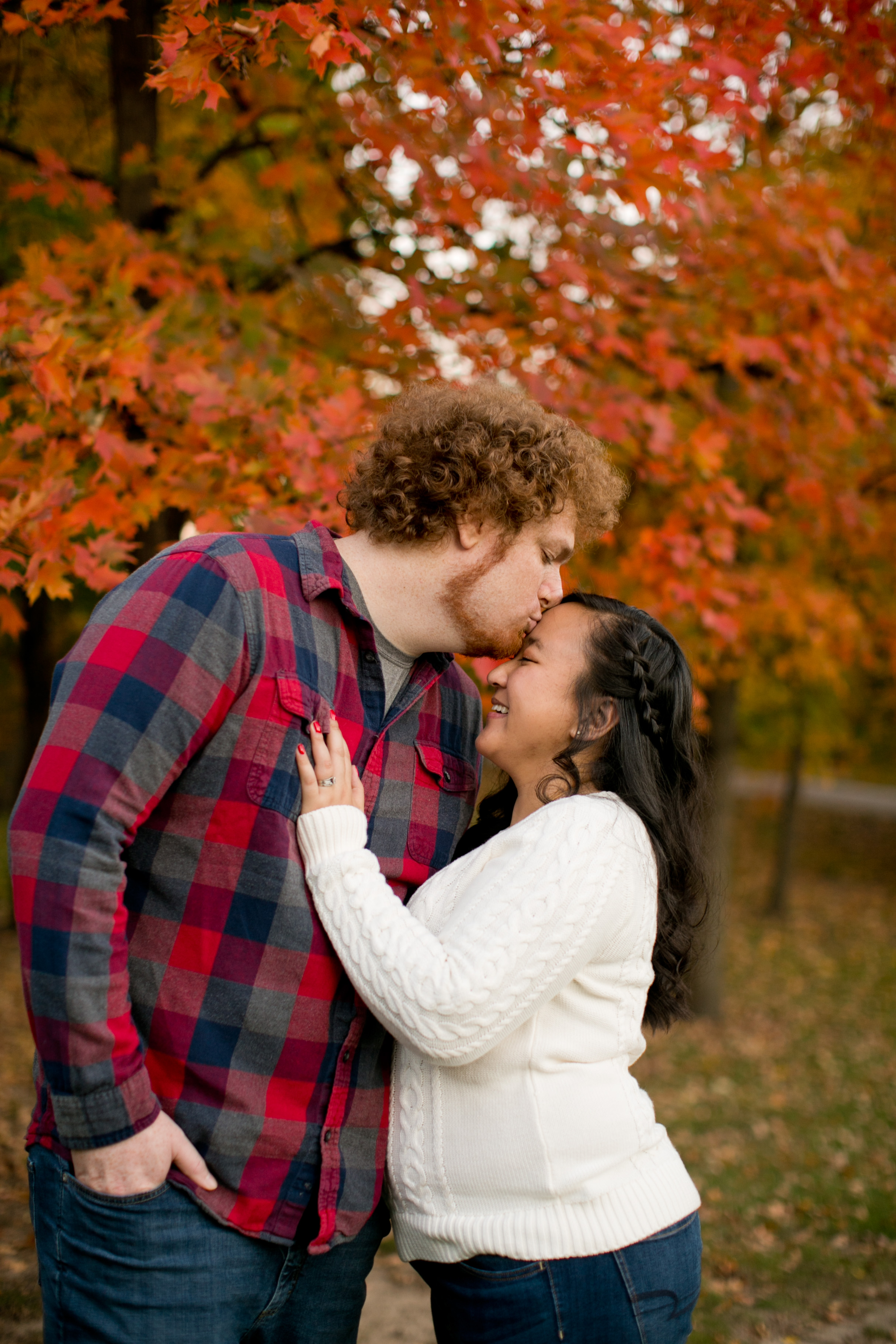 groom kissing bride on forehead in front of fall trees ames iowa state university