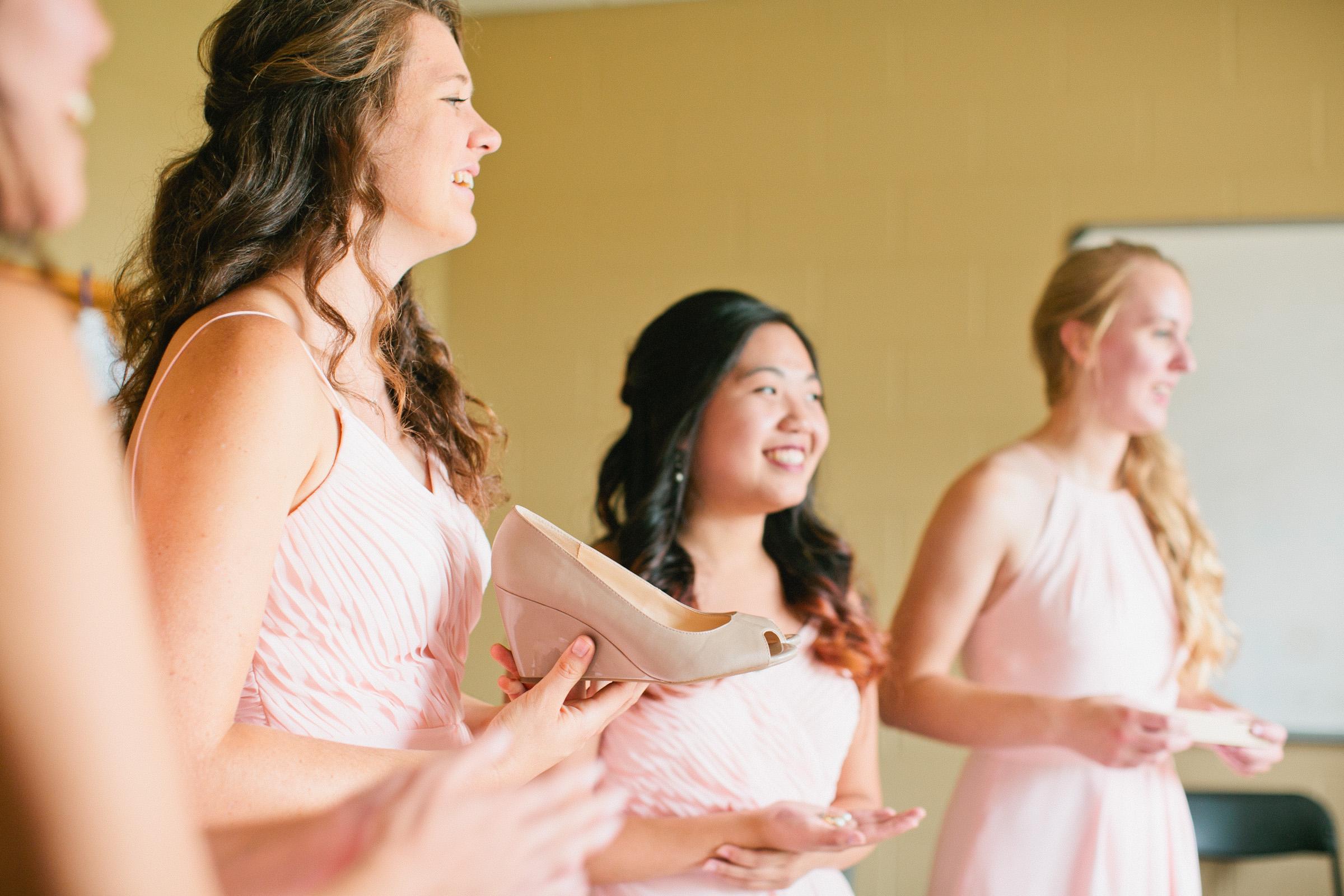 light pink dresses bridesmaids helping bride in to her wedge heels