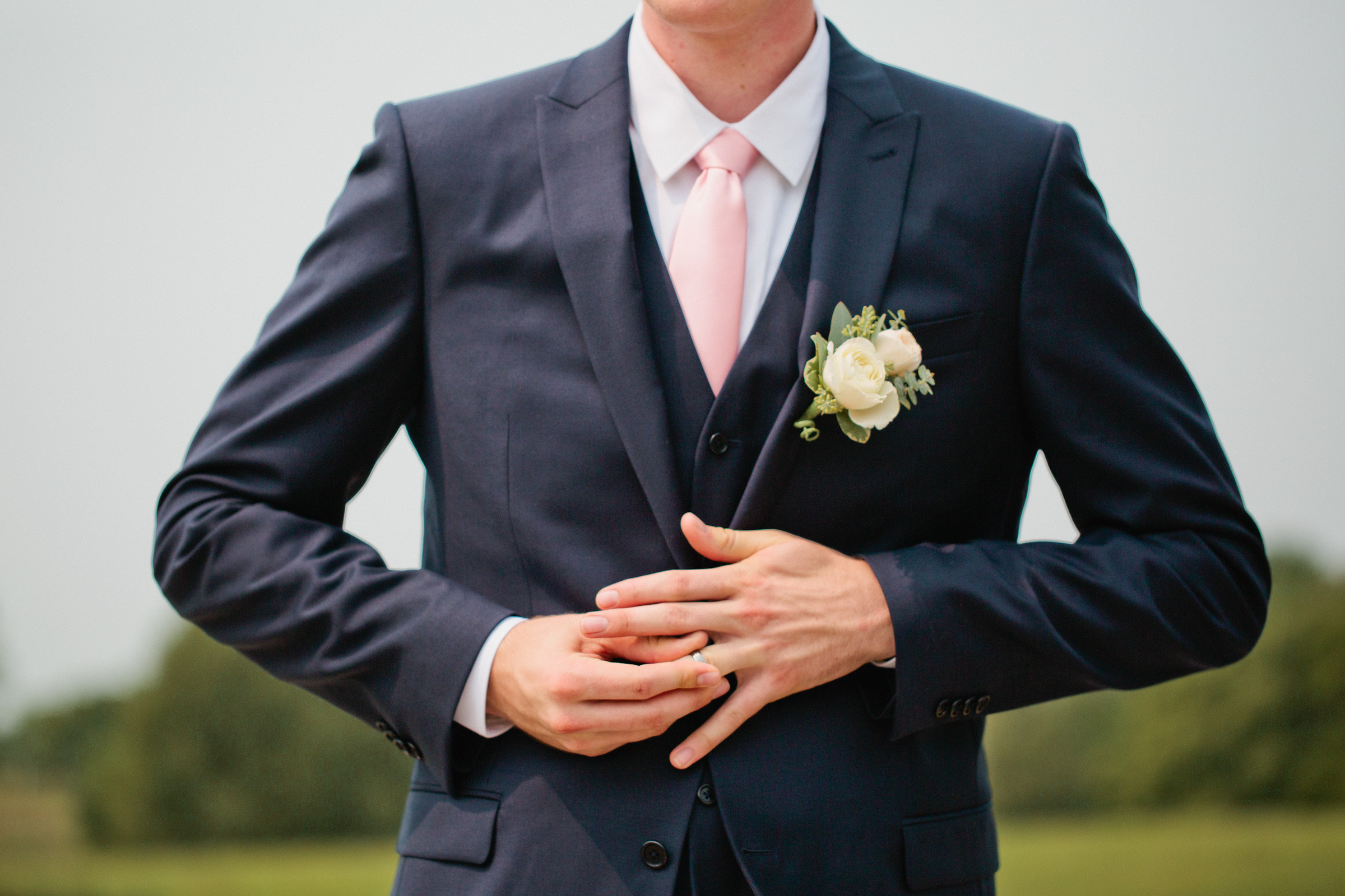 groom in navy suit and pink tie fiddling with wedding ring