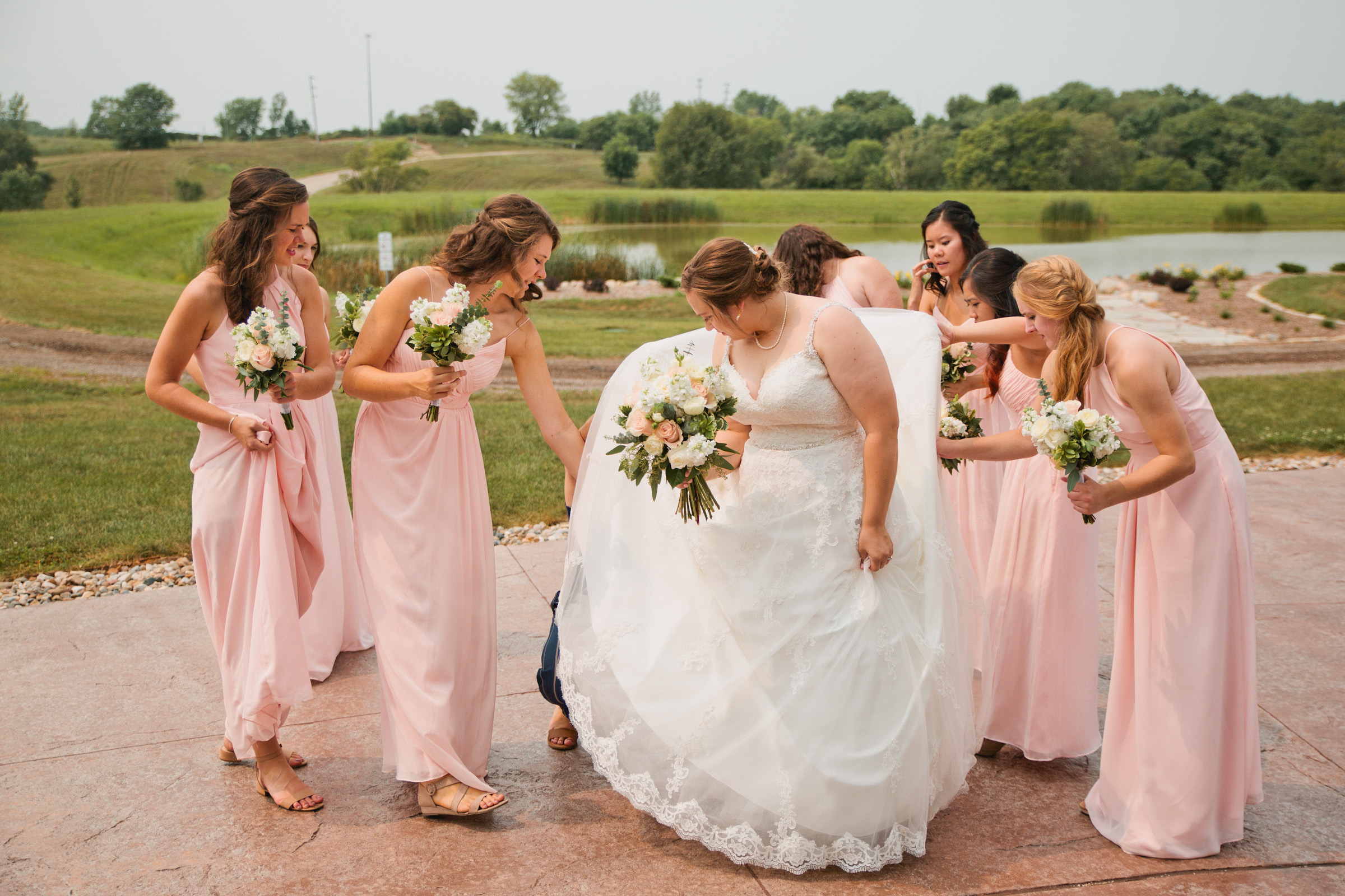 bridesmaids helping bride get bugs out of her dress layers