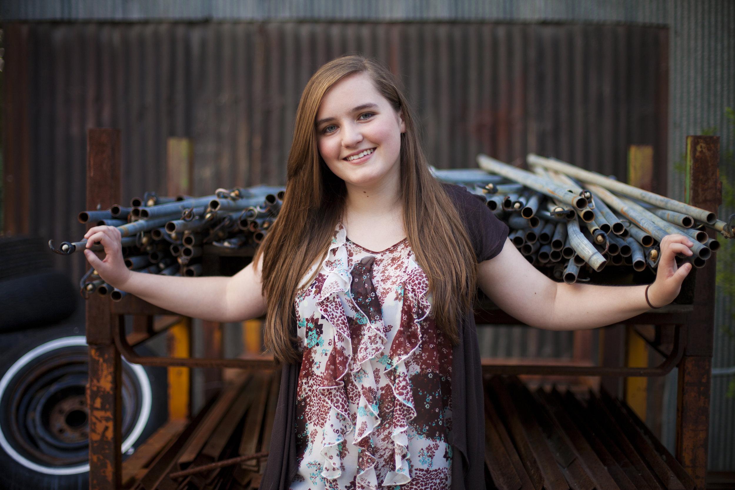 girl wearing white ruffle shirt standing by metal pipes senior photos