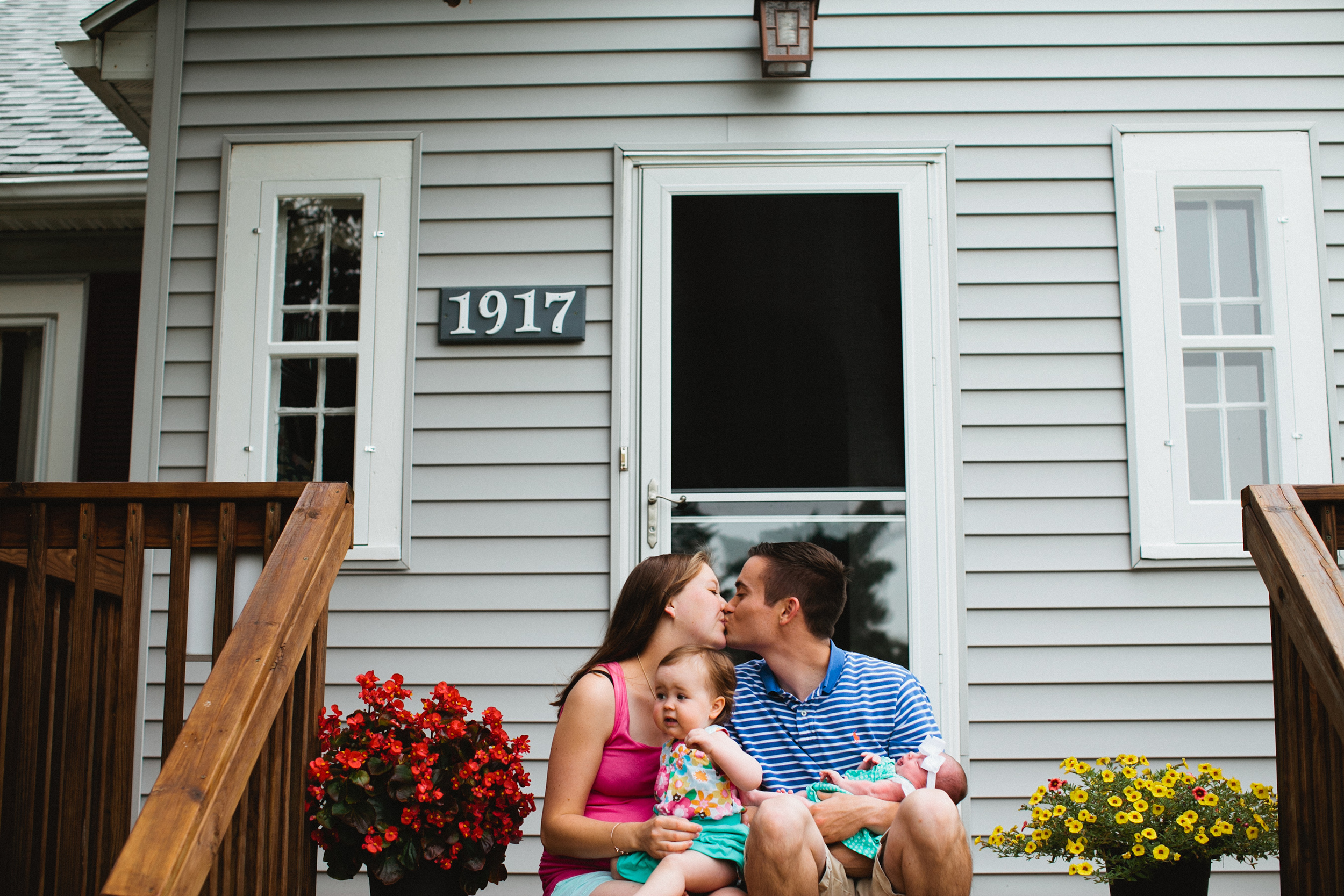 family sitting on front porch kissing with new baby and flowers in planters