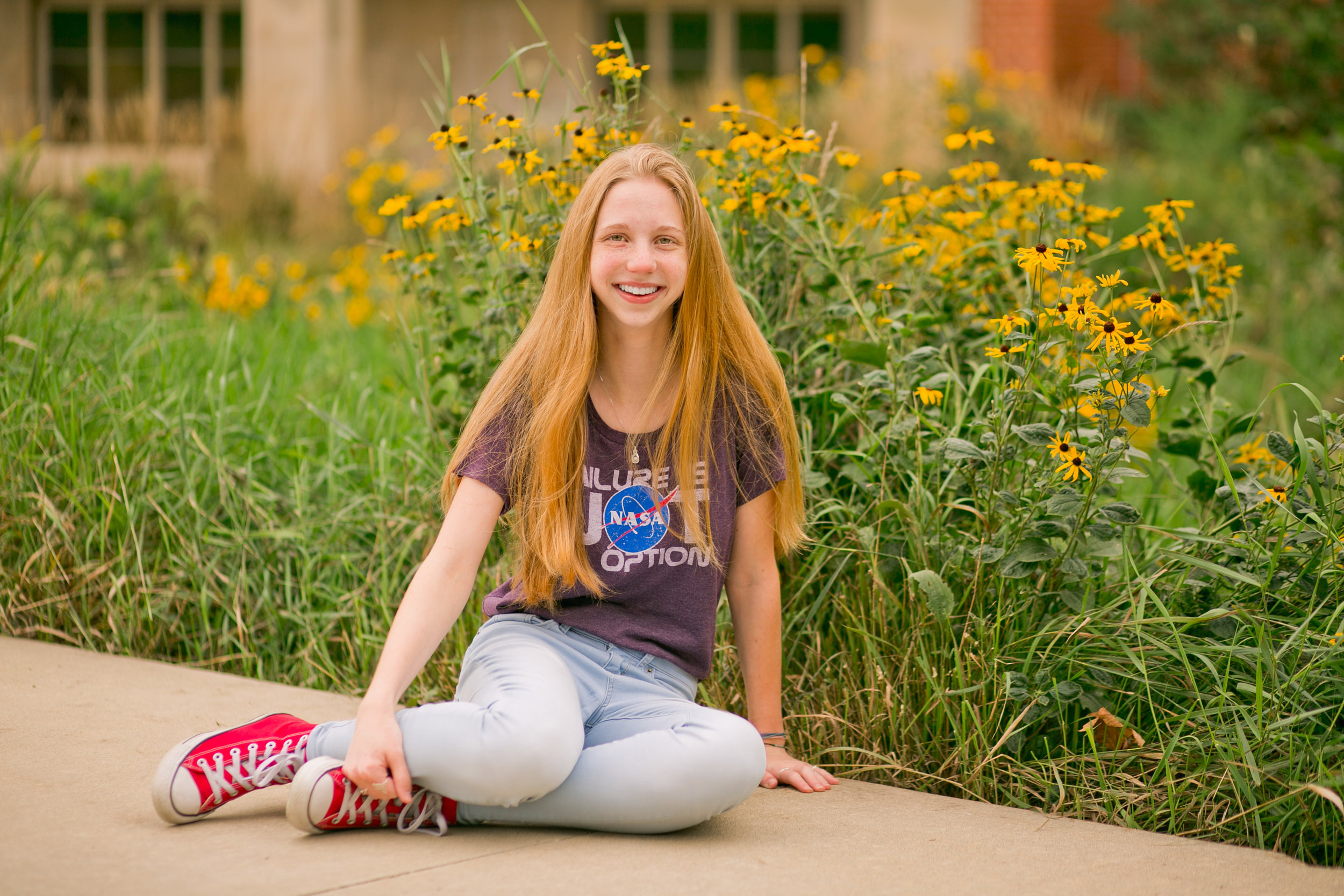 senior girl with long red hair sitting in front of yellow flowers and green grass