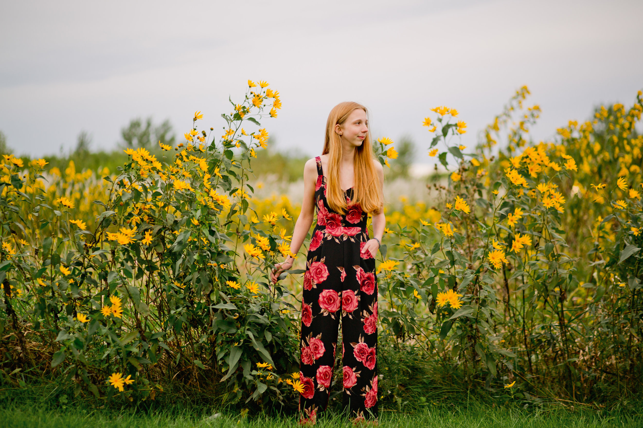 epic senior photos in Cedar Falls park with flowers and flower jumpsuit