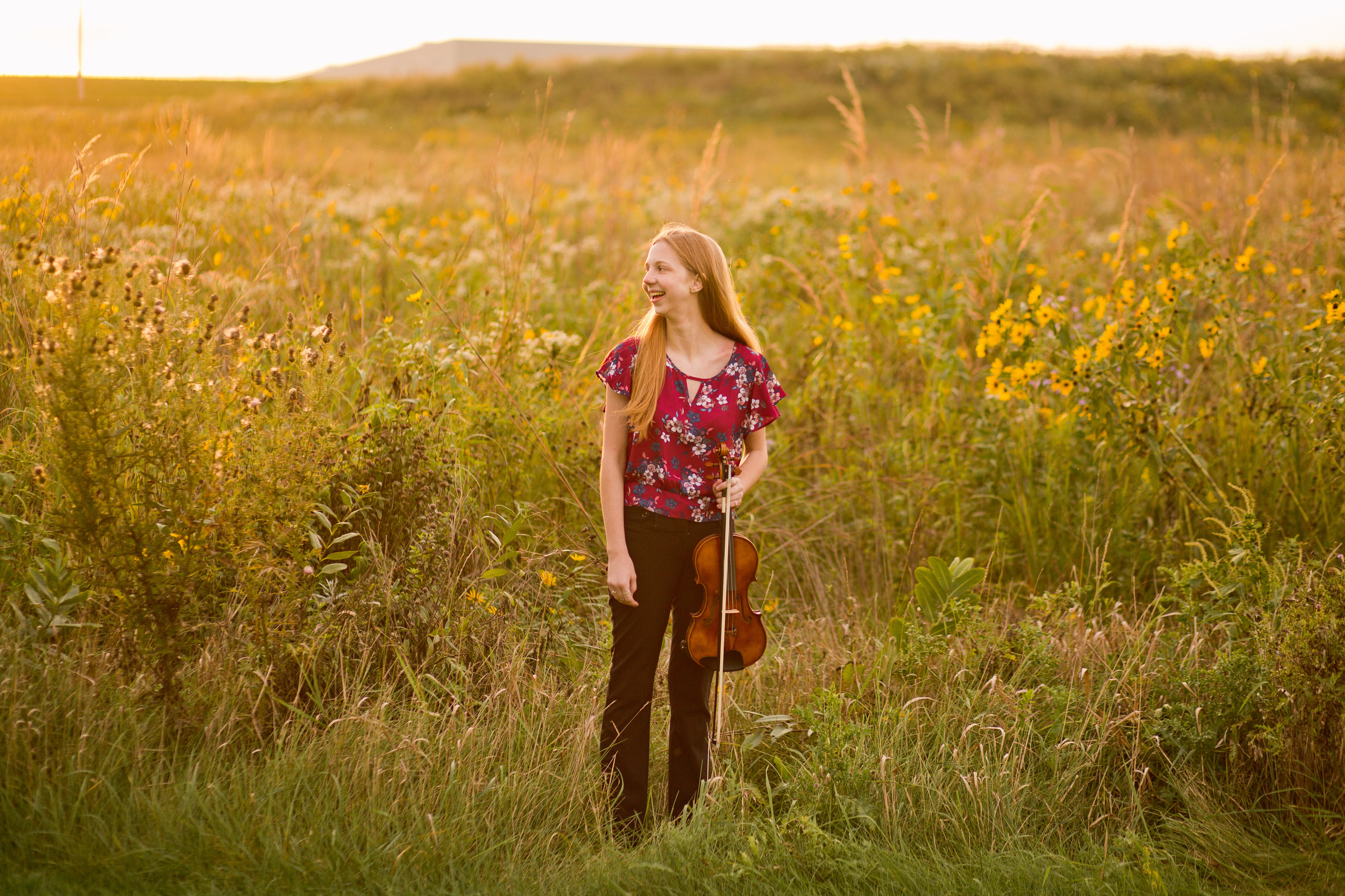 waukee senior high school senior photos . girl in field with violin at sunset wearing pink floral shirt