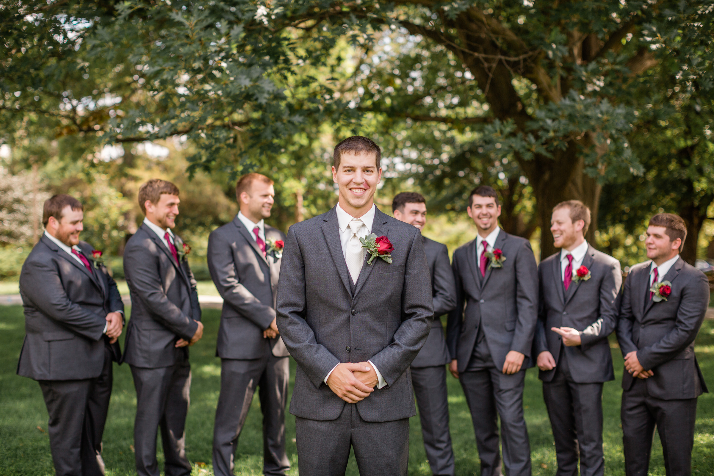 groom and groomsmen laughing together outside iowa state university wedding ames iowa