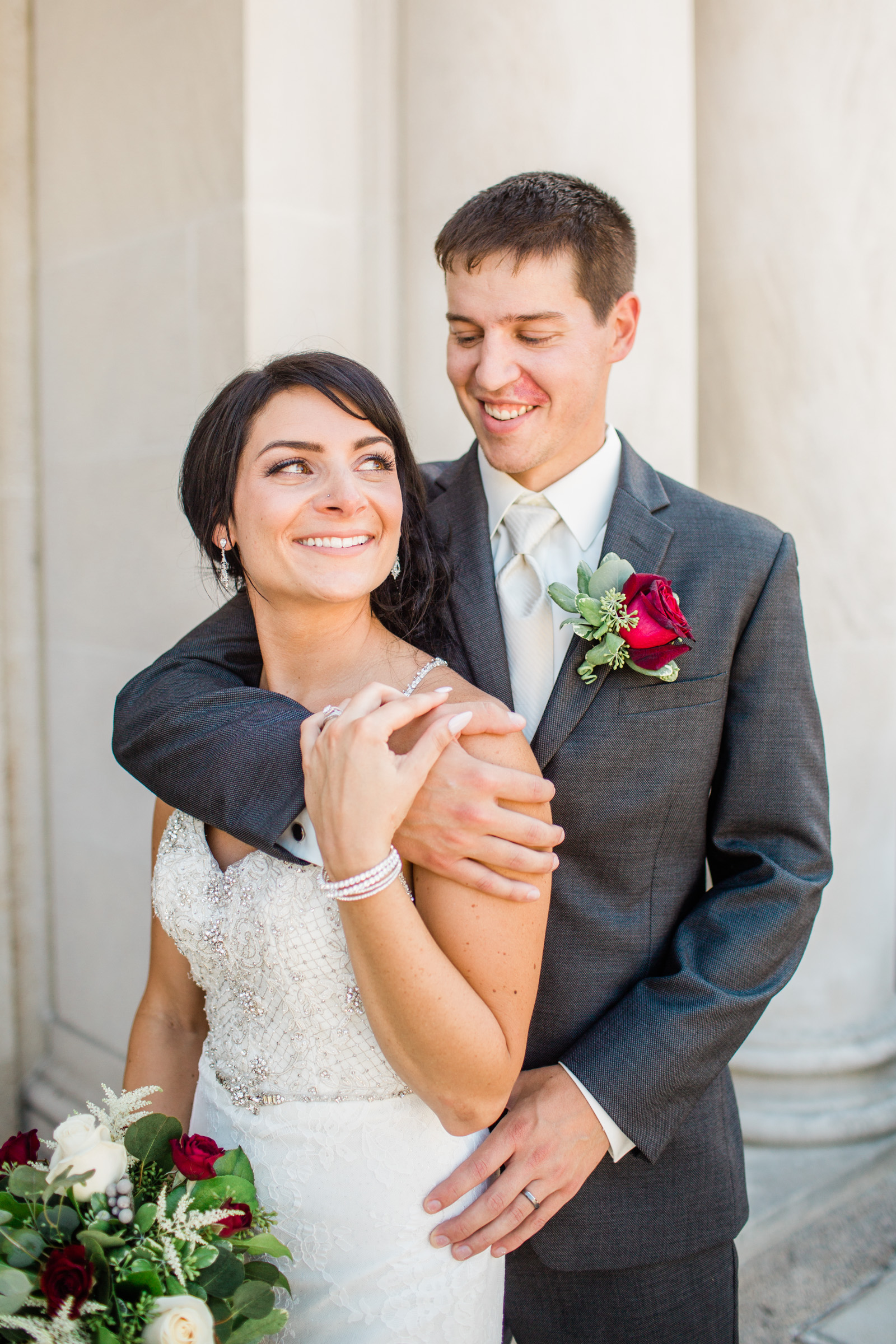 groom hugging bride while they both smile and bride holds flowers wedding Des Moines