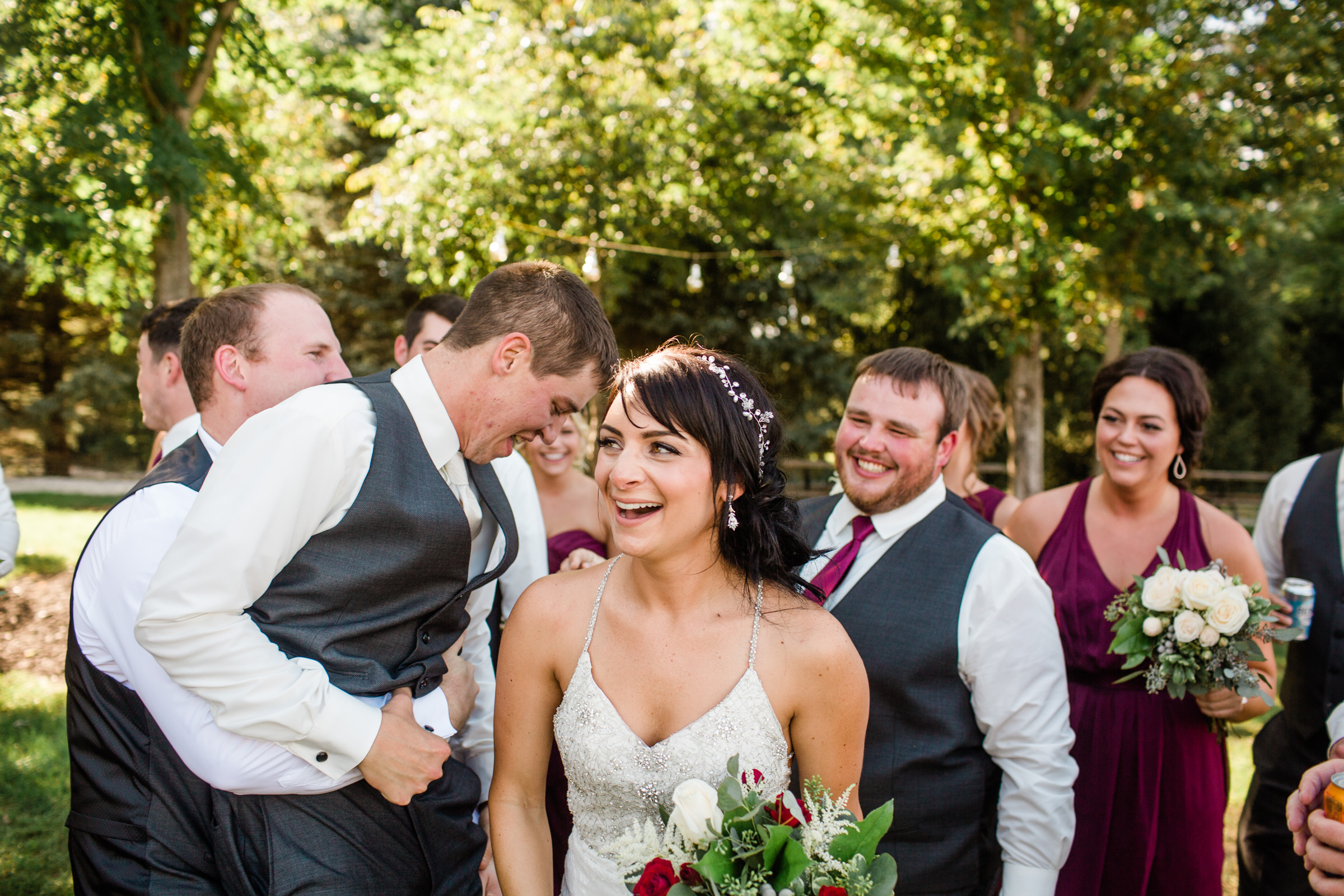 bride laughing at husband and bridal party outdoor weddings Iowa