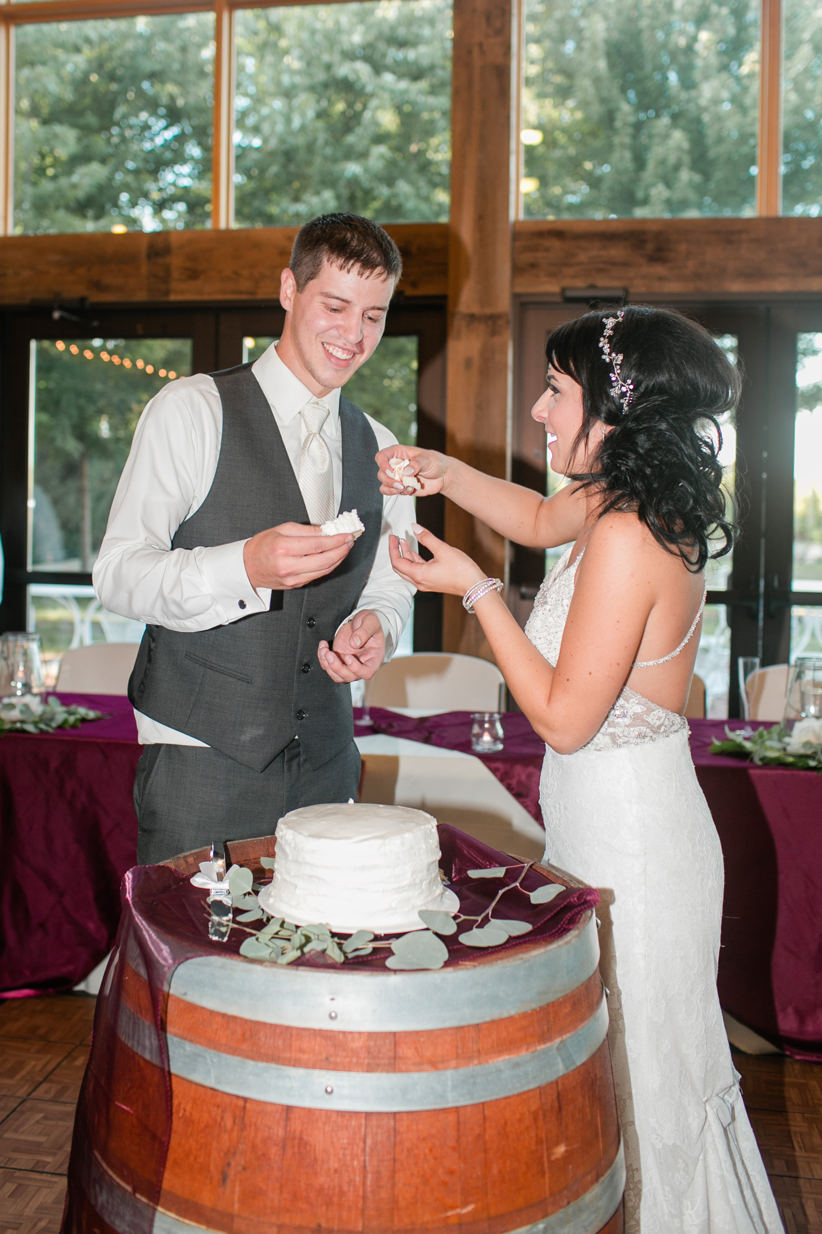 bride and groom cutting cake and smashing it in faces