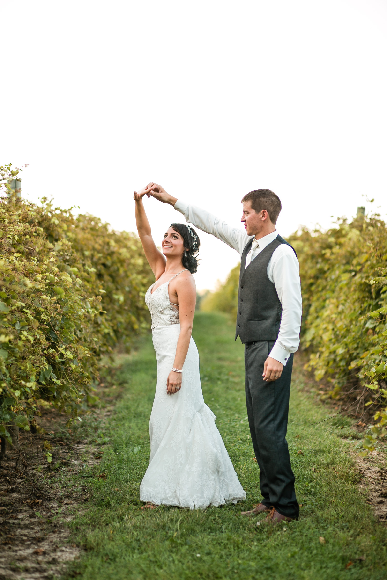 bride dancing outside with husband at vineyard wedding sunset