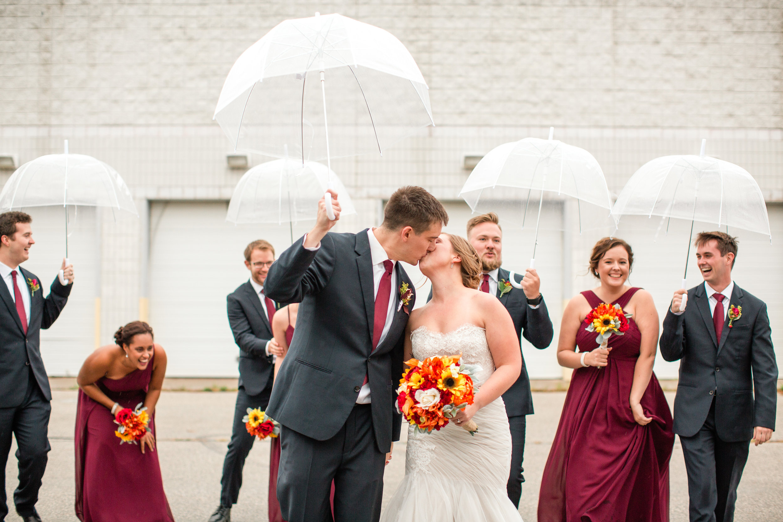 rainy day wedding with clear umbrellas bride groom kissing