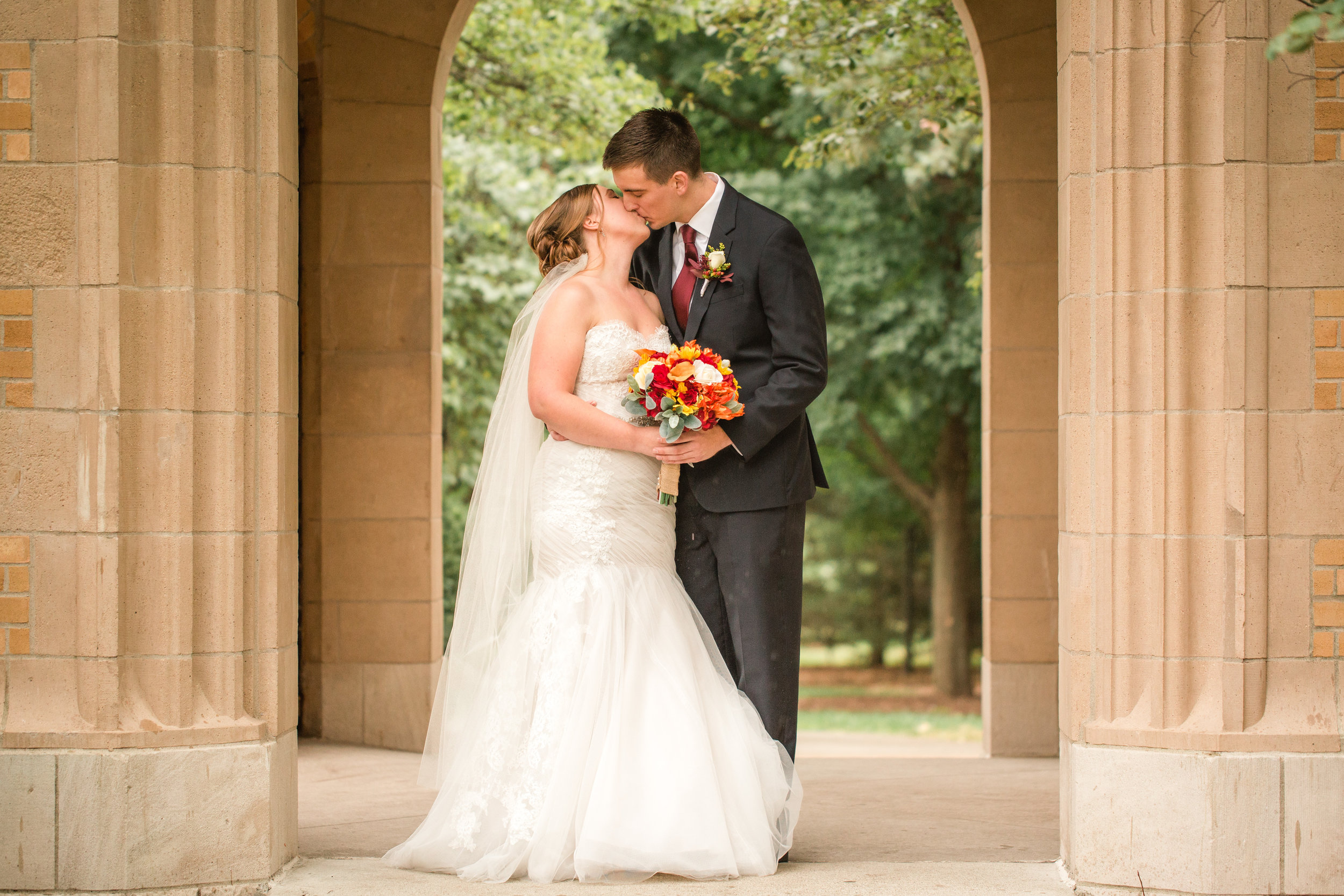 bride and groom kissing under iowa state campanile