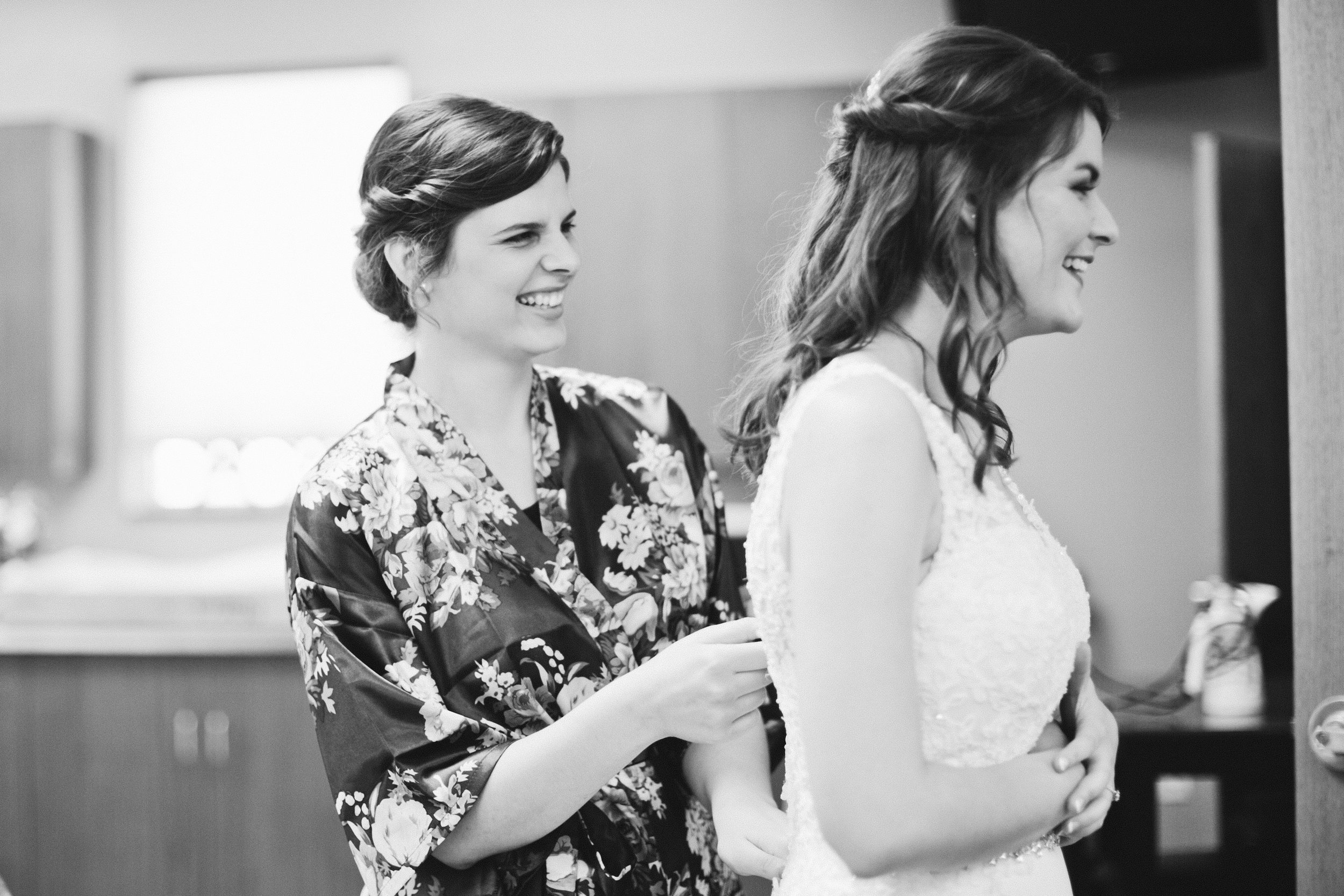 maid of honor helping sister in to her dress