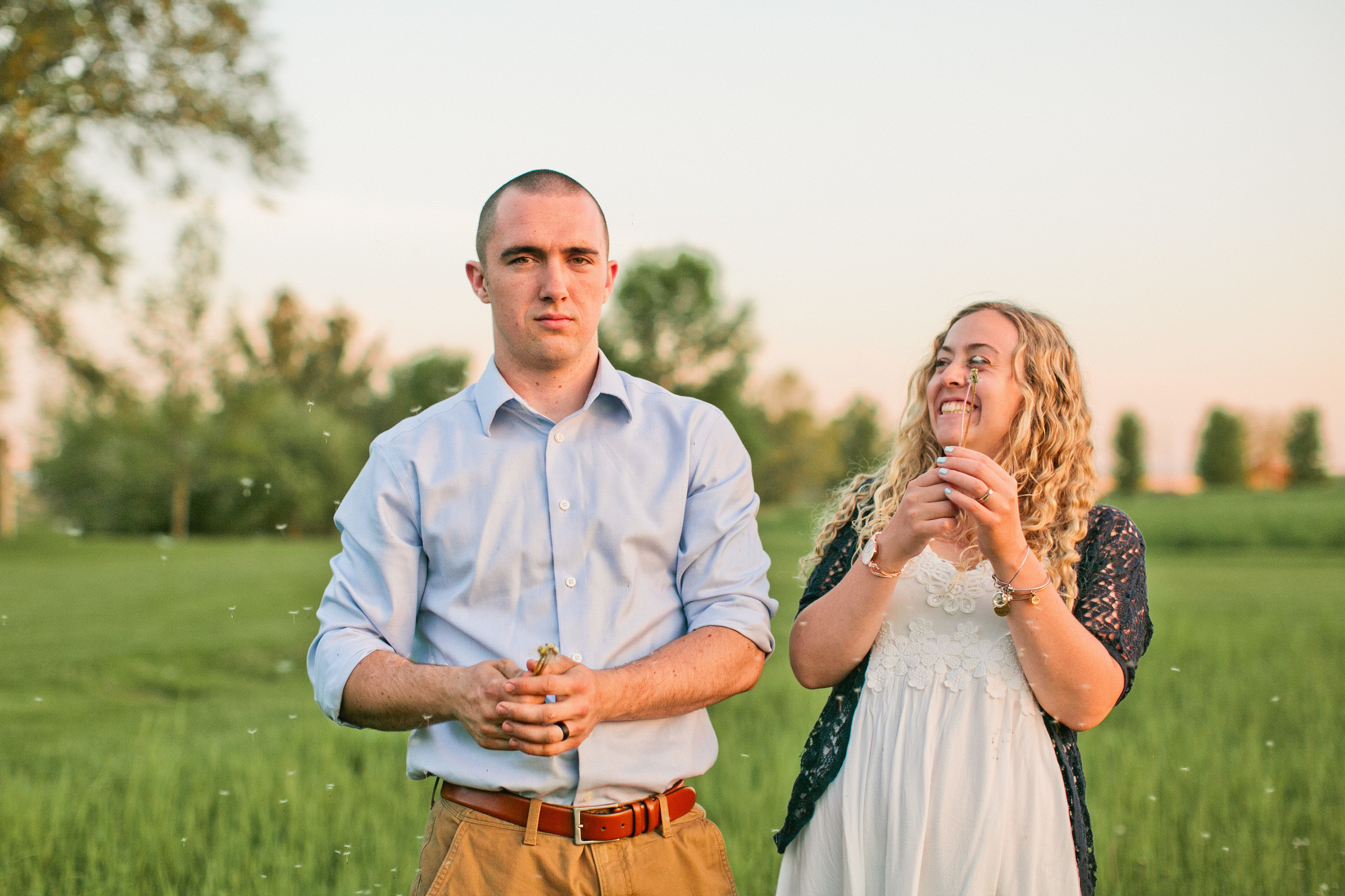 couple blowing dandelions in field engagement photos saylorville iowa