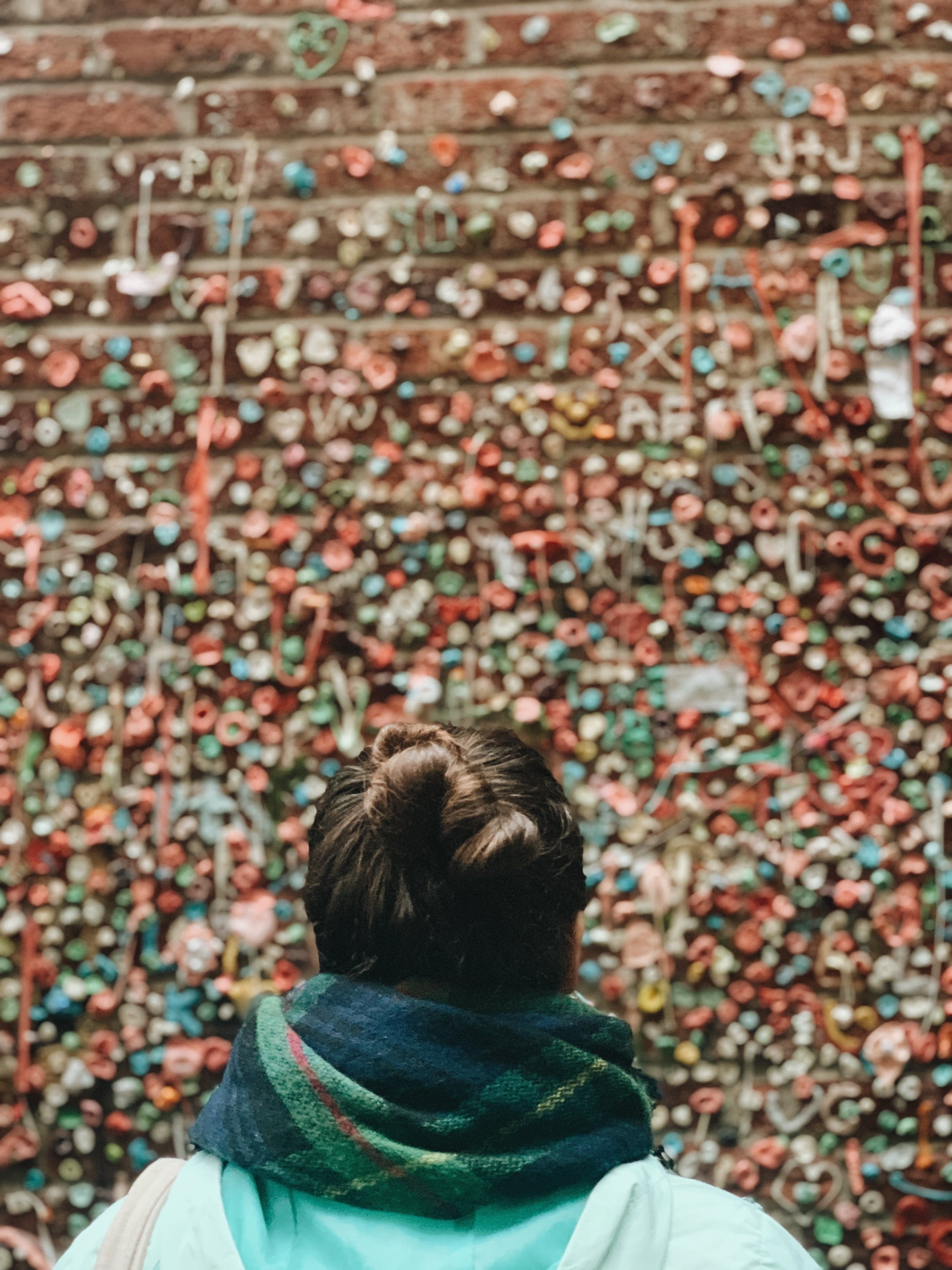 girl at the gum wall in seattle tourist from behind