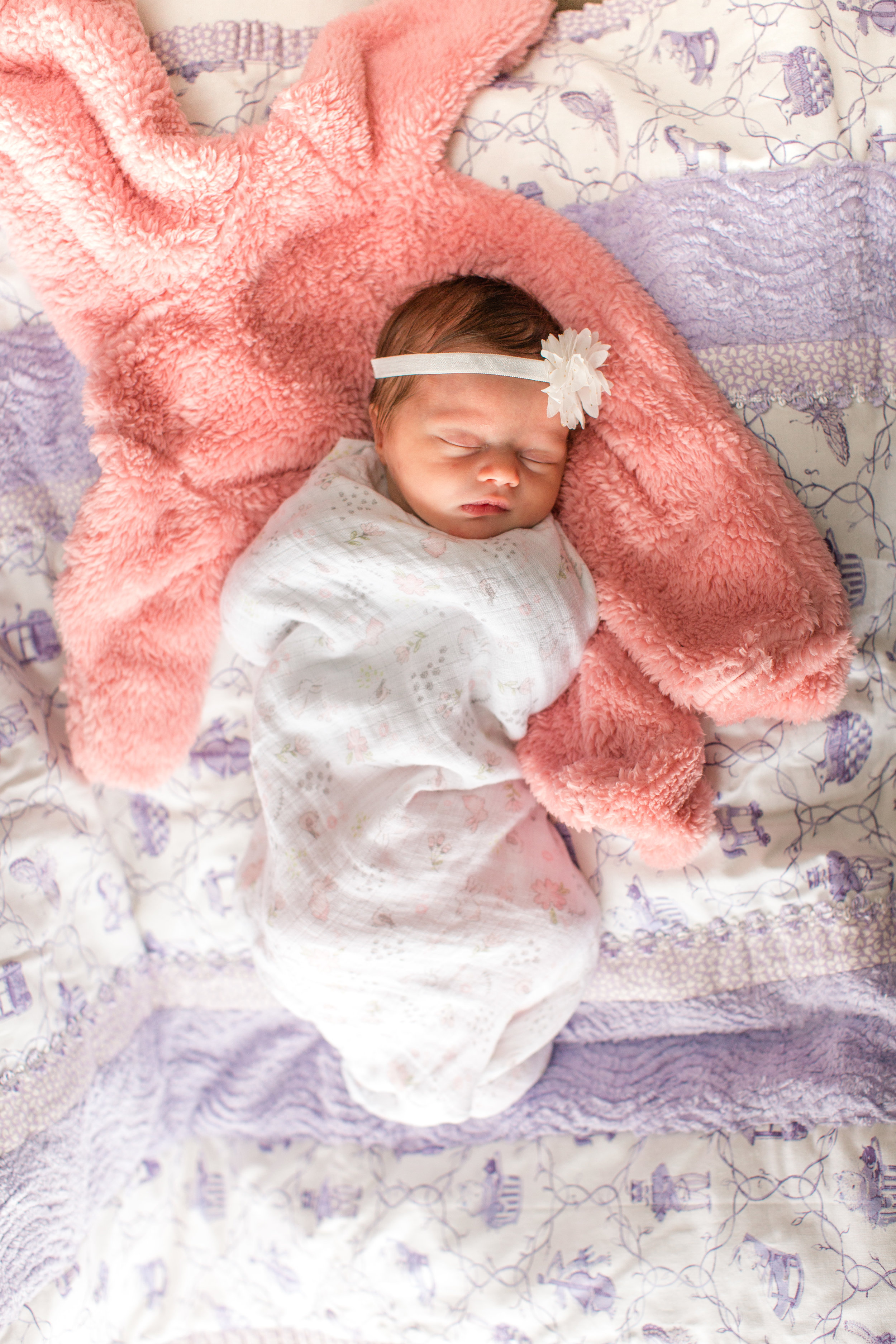 sweet newborn photo on handmade quilt and pink baby snowsuit