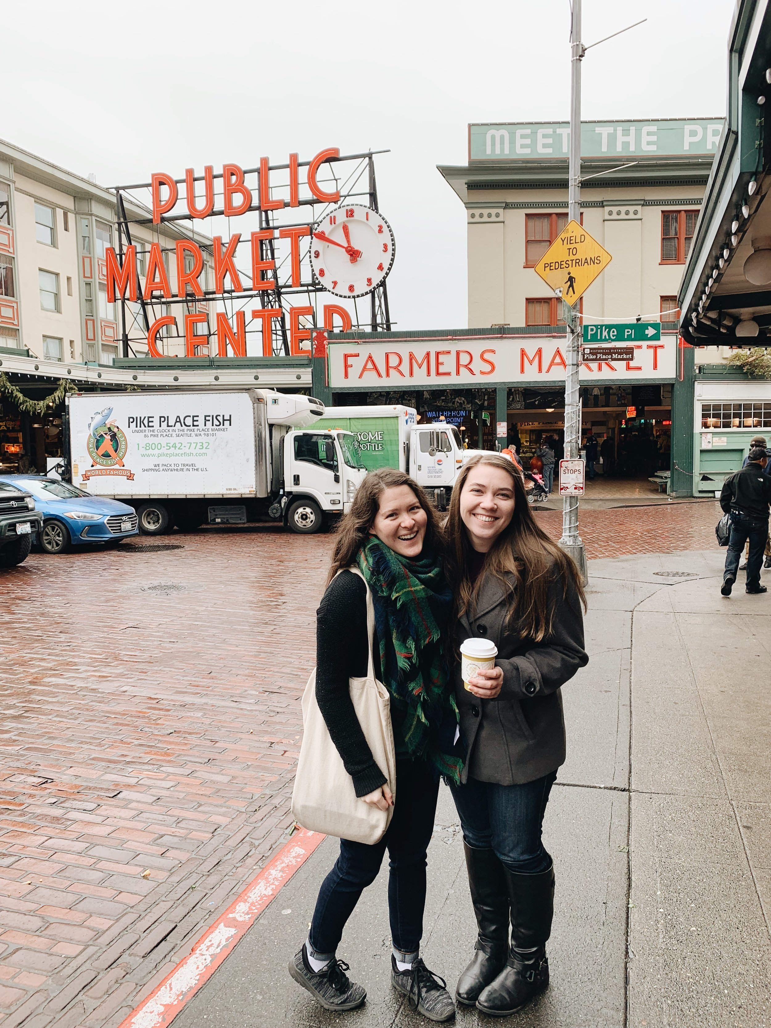 heather and i with coffee in front of the seattle public market sign