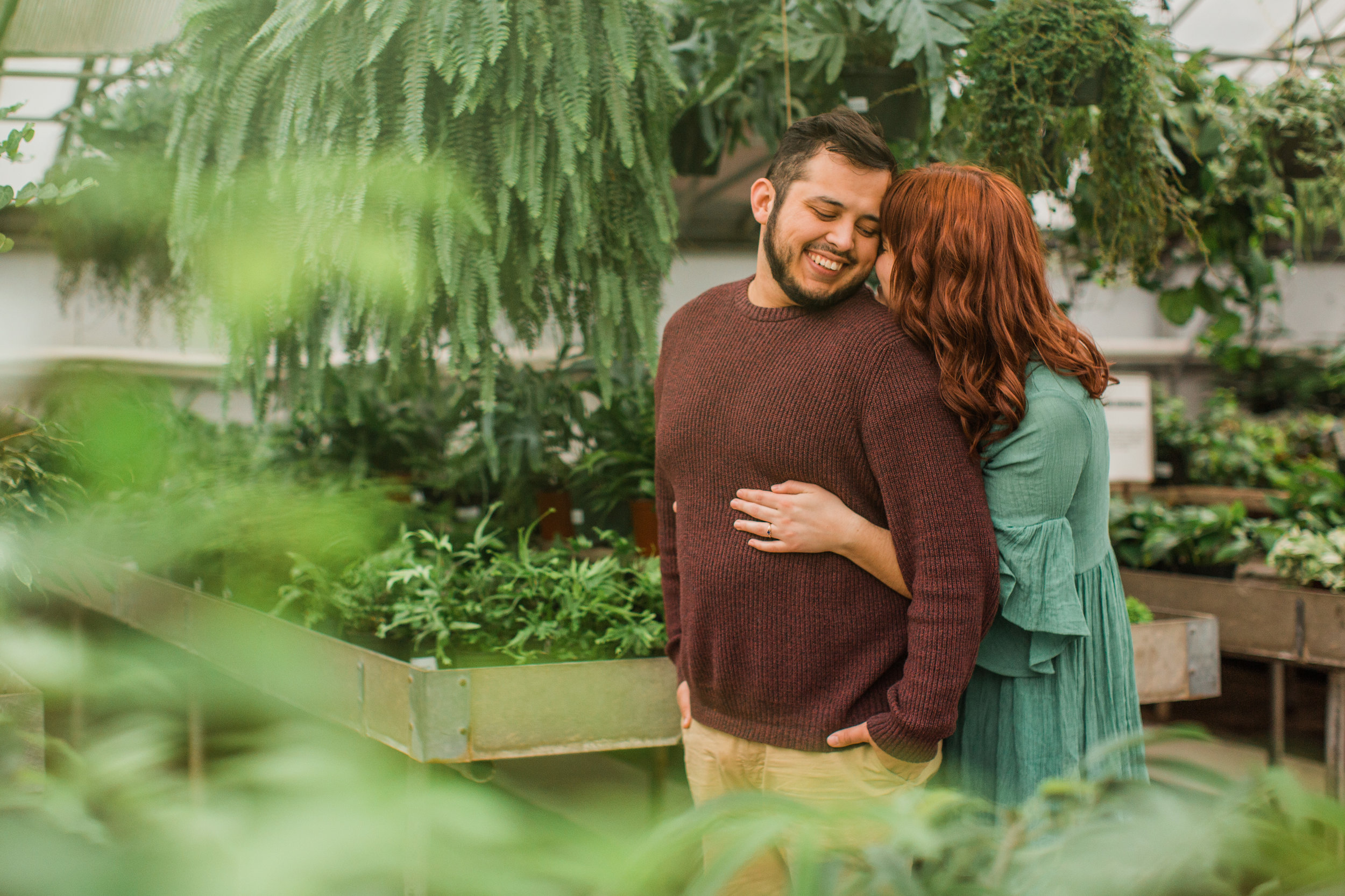 cute engaged couple hugging in greenhouse des moines iowa engagement pictures