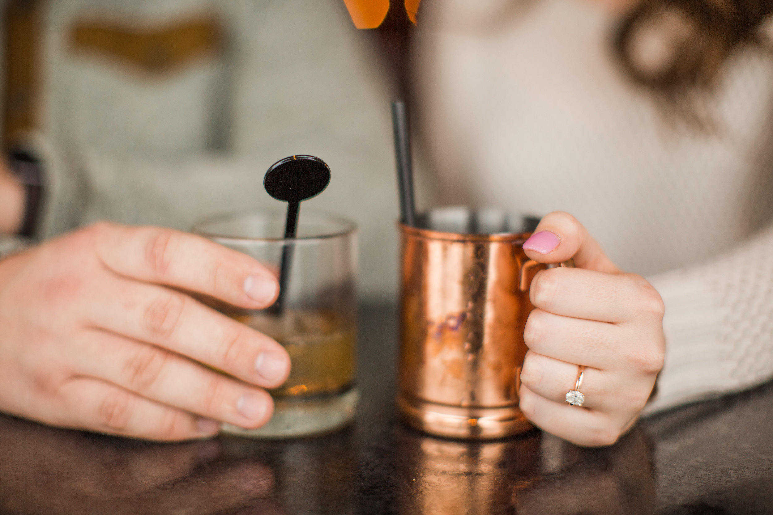 hands holding drink glasses whiskey Moscow mule engagement ring oval diamond rose gold ring