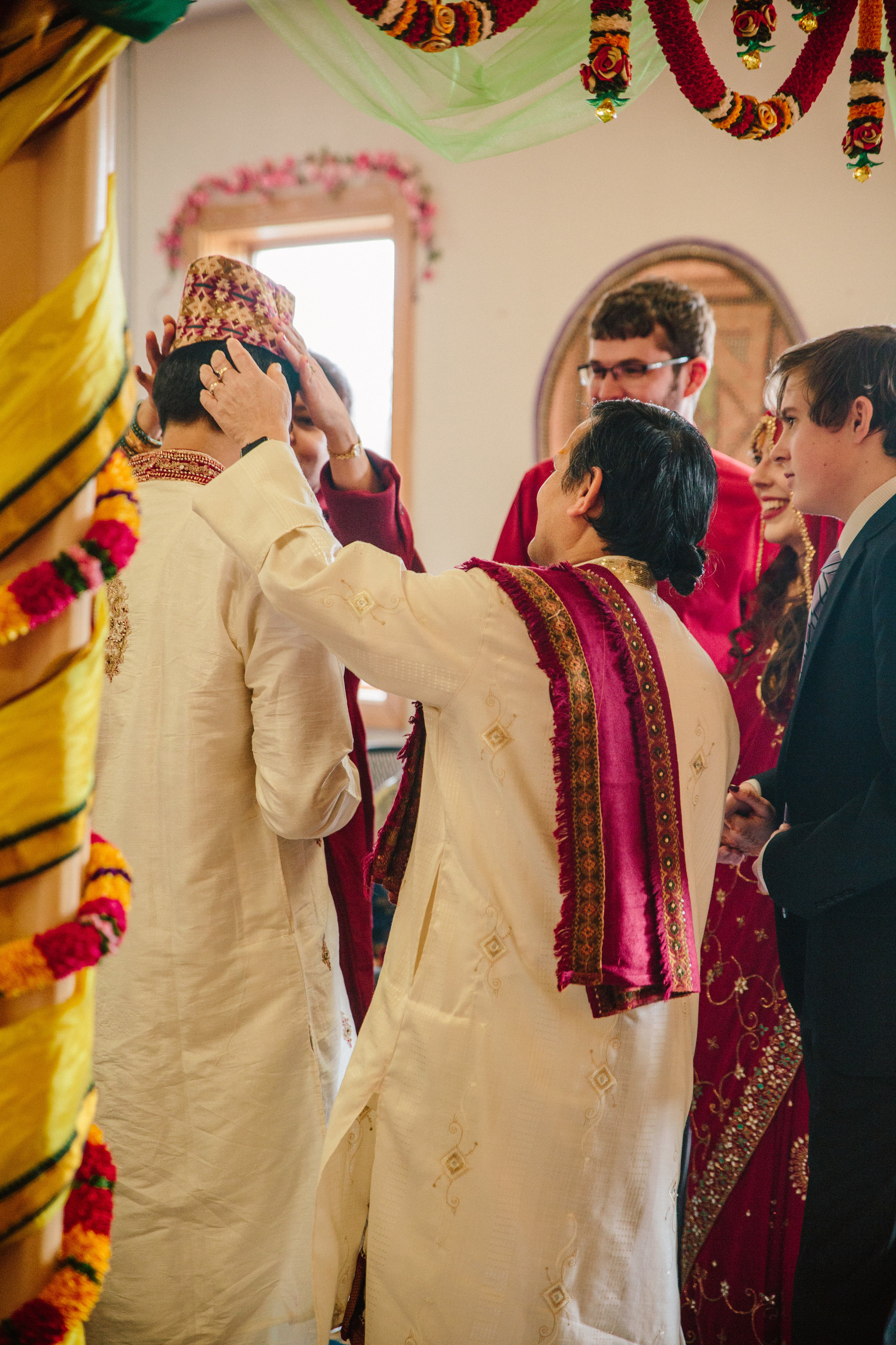 Father of the groom gives traditional Nepali cap to son during wedding ceremony des moines photographers