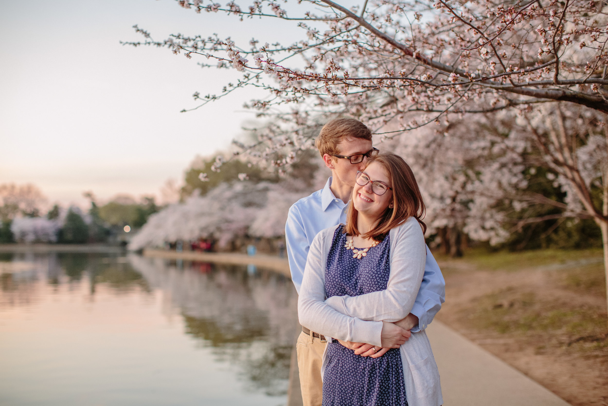 guy and girl hugging under blooming cherry tree Washington DC tidal