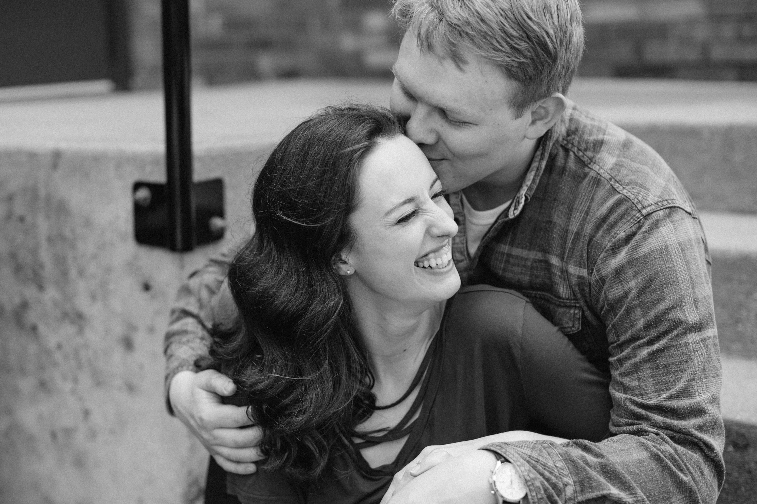 couple kissing and snuggling sitting on steps downtown des moines engagement pictures
