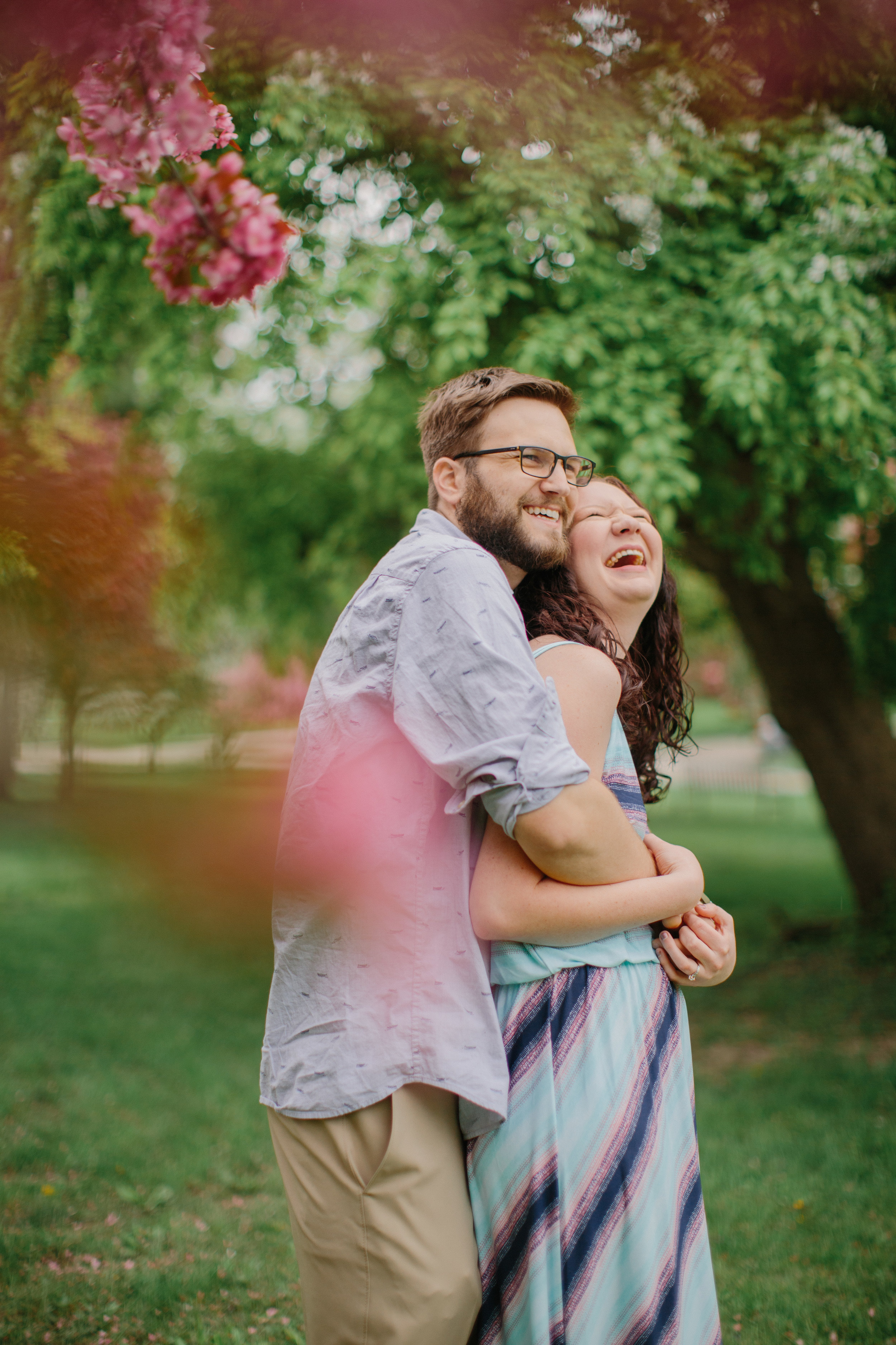 bride and groom laughing engagement photos with pink cherry blossoms des moines iowa