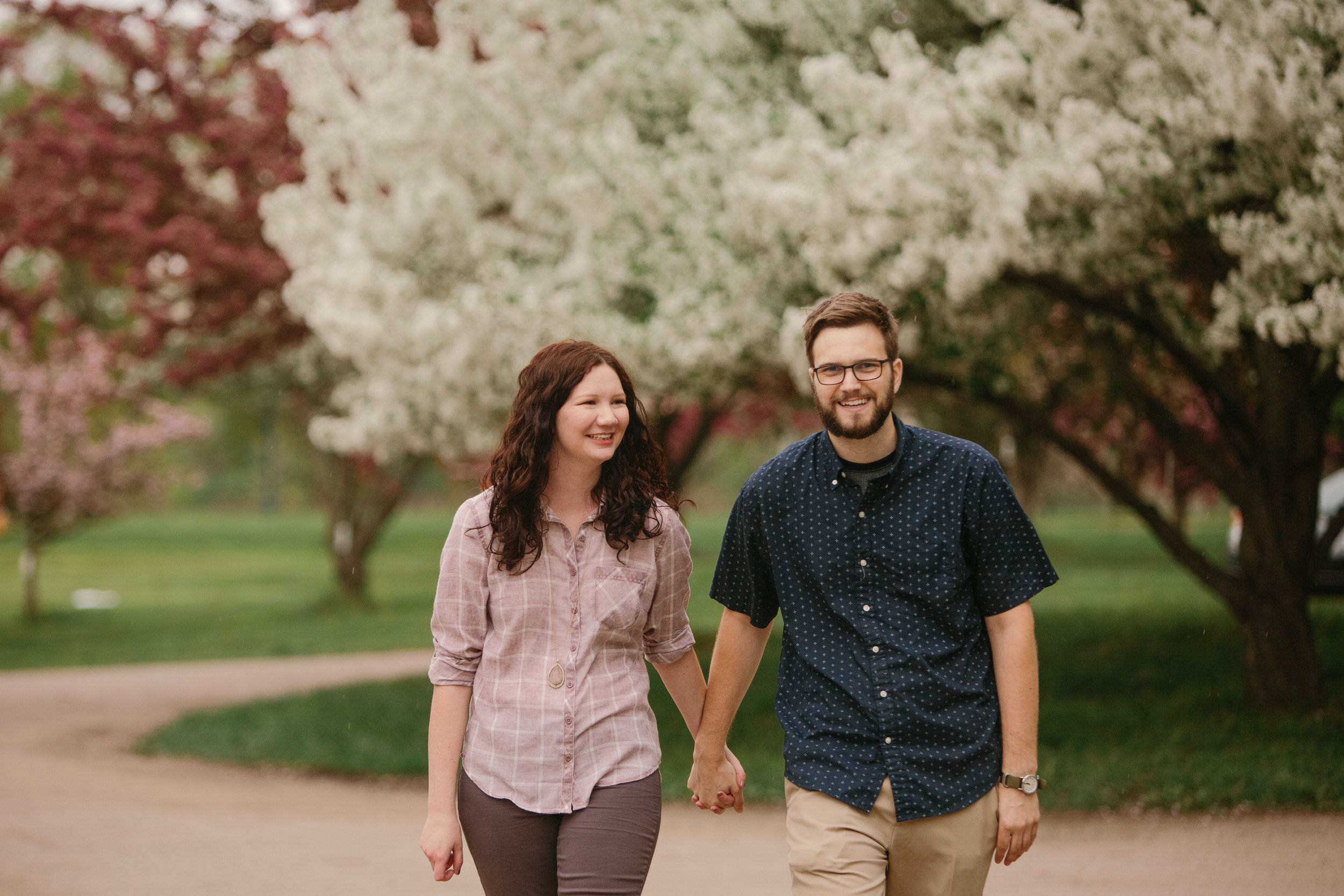 couple walking and smiling engagement photos iowa des moines cedar falls