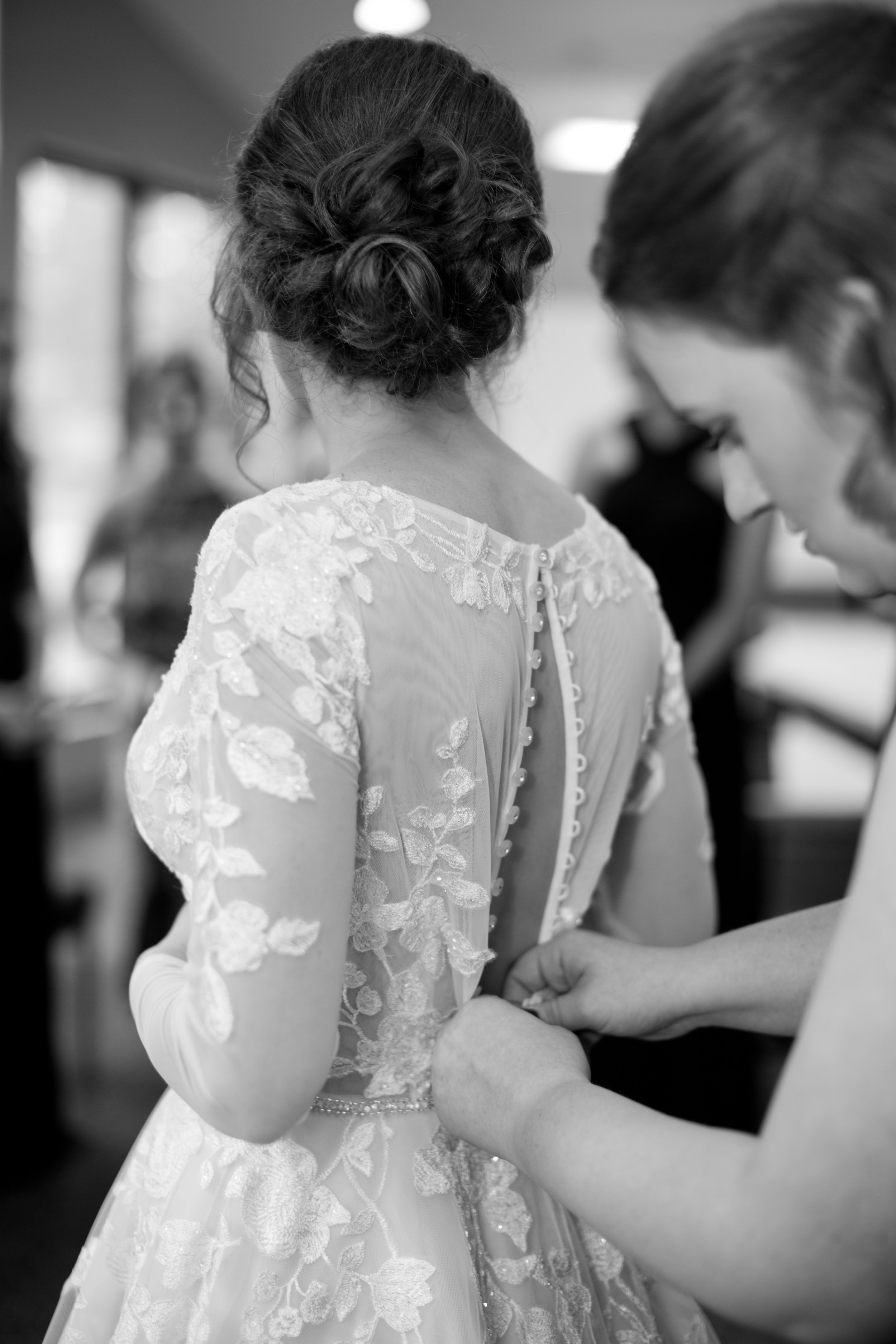 bride buttoning her wedding dress with sister // Osceola wedding photographer amelia renee