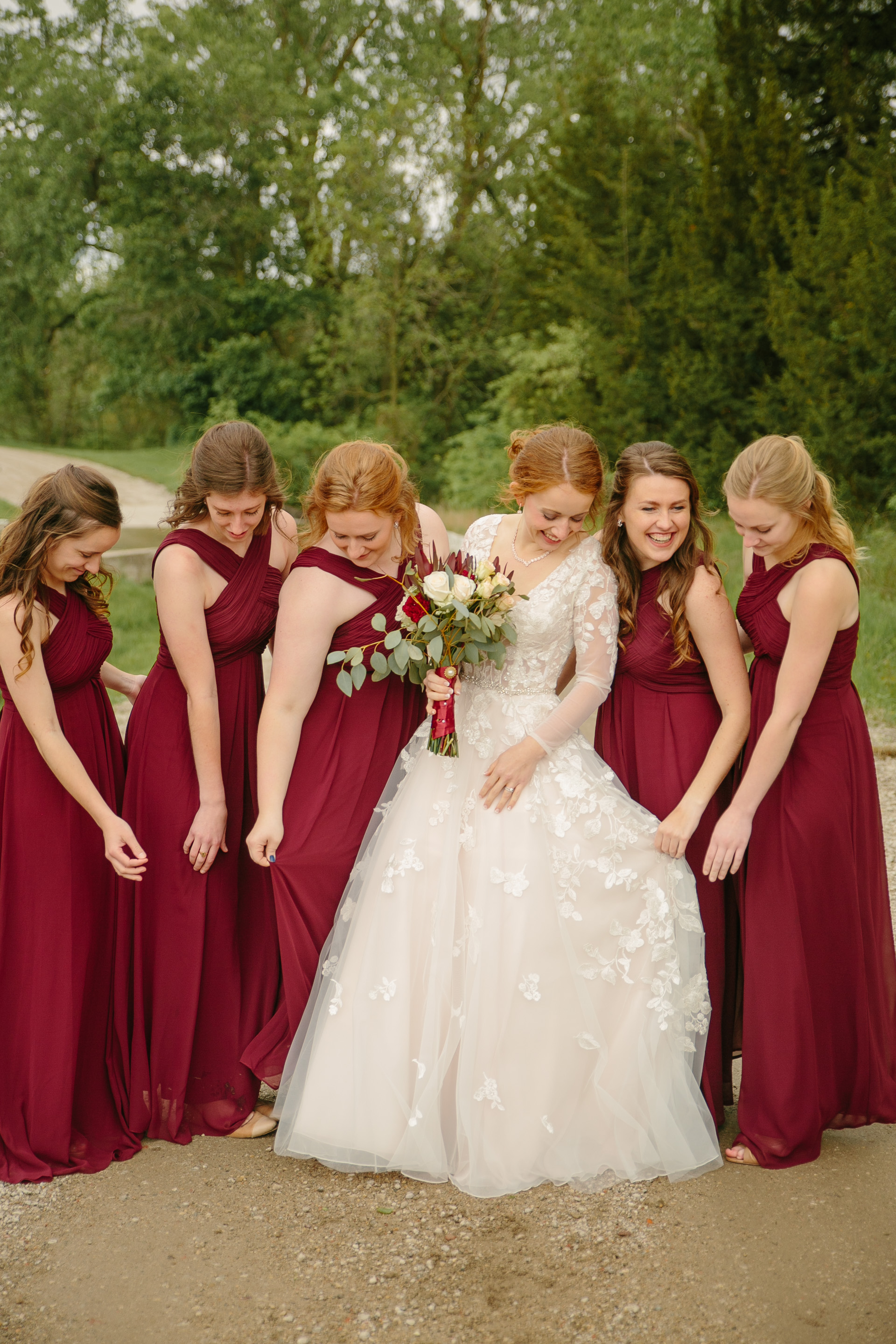 bride and bridesmaids in burgundy wine dresses at outdoor weddin in des moines