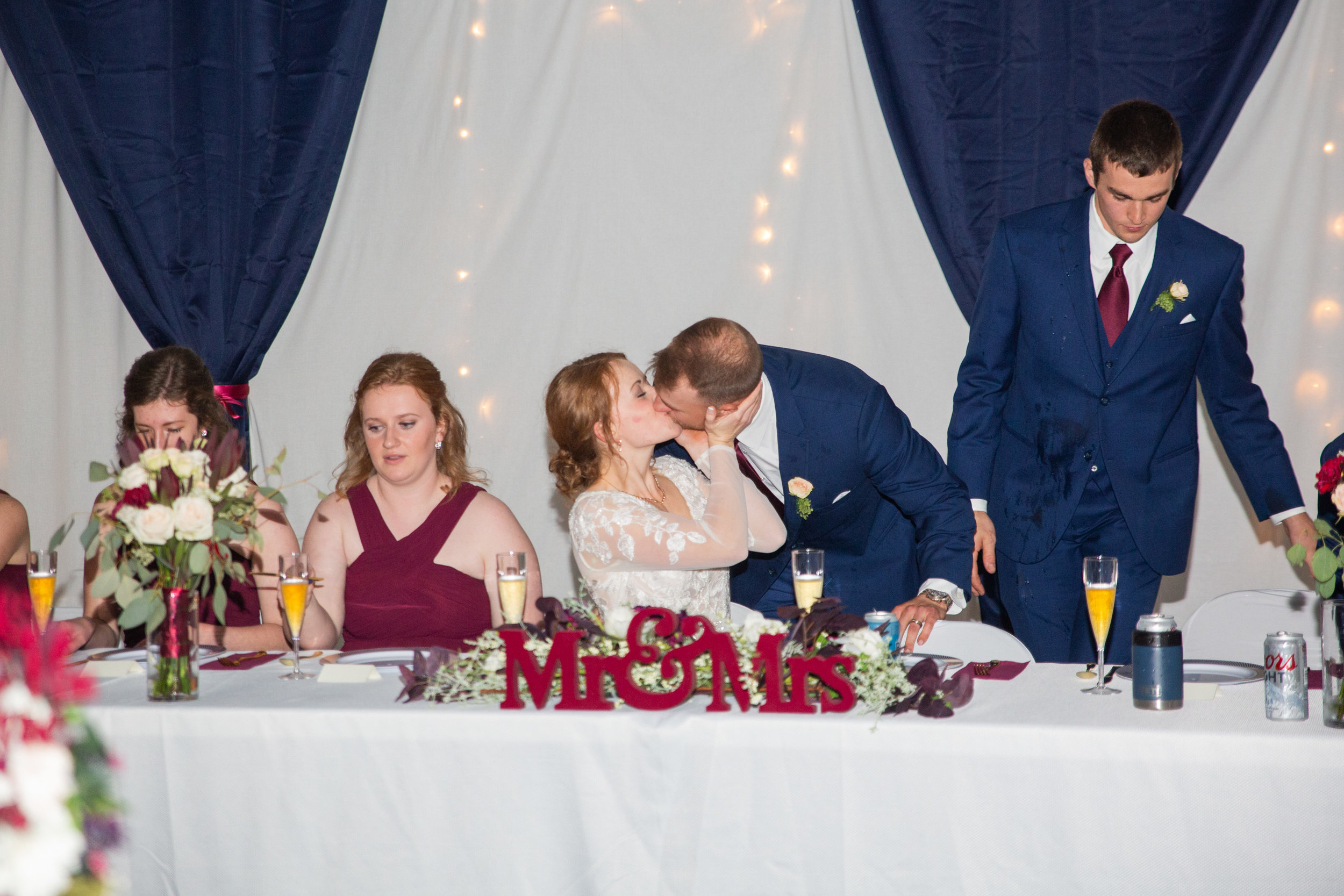 bride and groom kissing at head table during reception wedding des moines venues